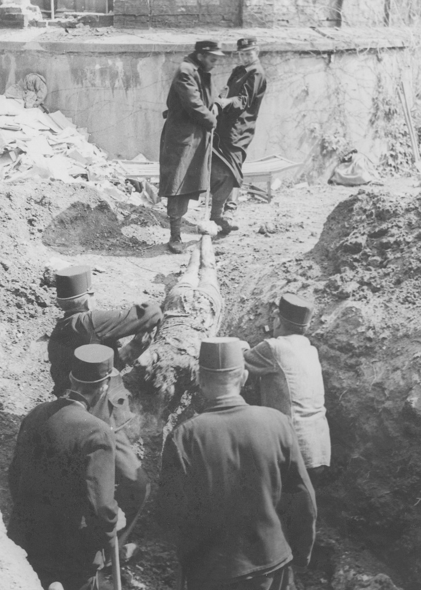 Hungarian gendarme exhume corpses of Jews from a mass grave.  The victims were killed in the Maros Street Hospital massacre.