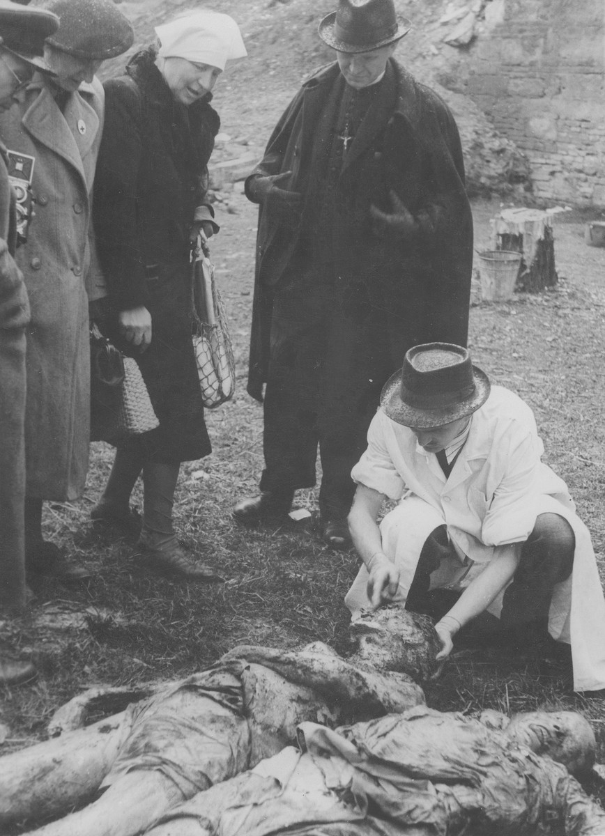Hungarian civilians identify the corpses of Jews exhumed from a mass grave.  The victims were killed in the Maros Street Hospital massacre.  The woman in the head scarf is Iren Kaufmann.  She is identifying the remains of her husband Zsigmond Kauffmann, who was a veterinary surgeaon and was a patient at the Maros utca hospital.  Standing beside her is her sister-in-law (Zsigmond's sister), Dr Iren Weisz. .