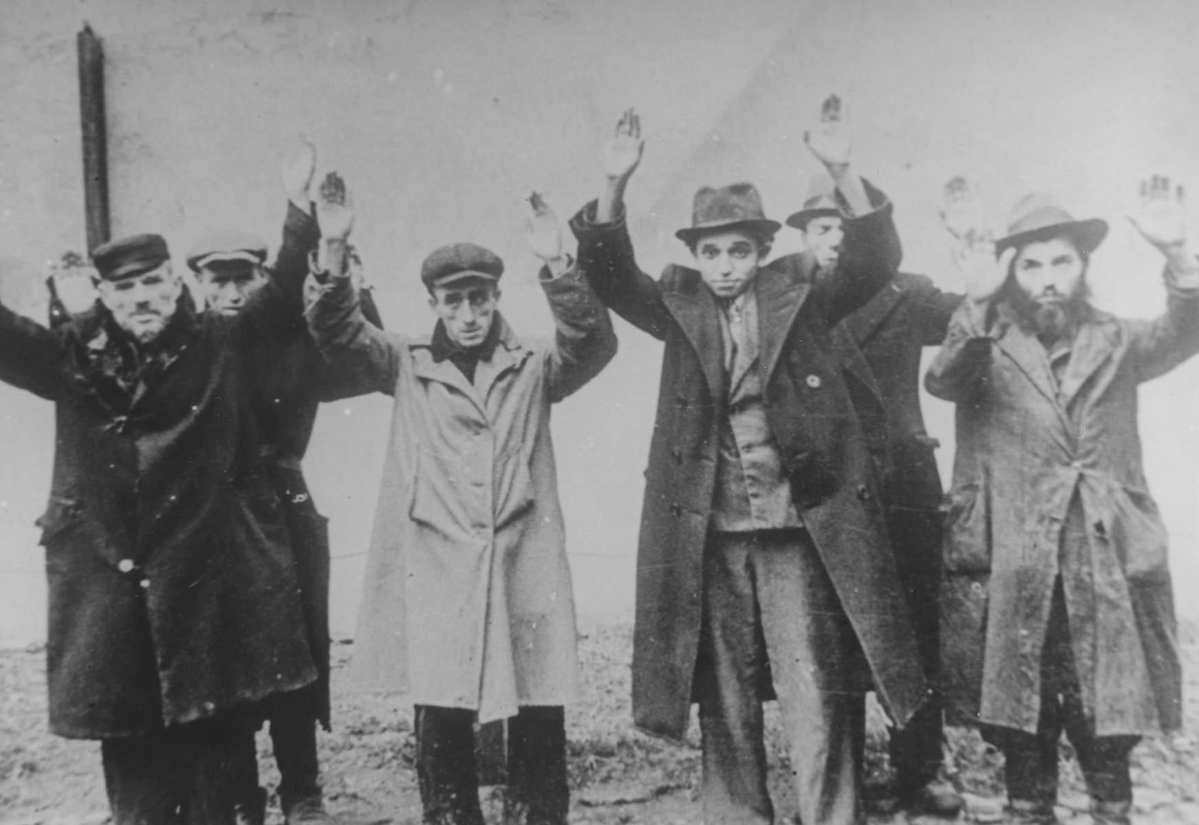 A group of Jewish men are forced to stand with their arms raised in an unidentified Polish town.