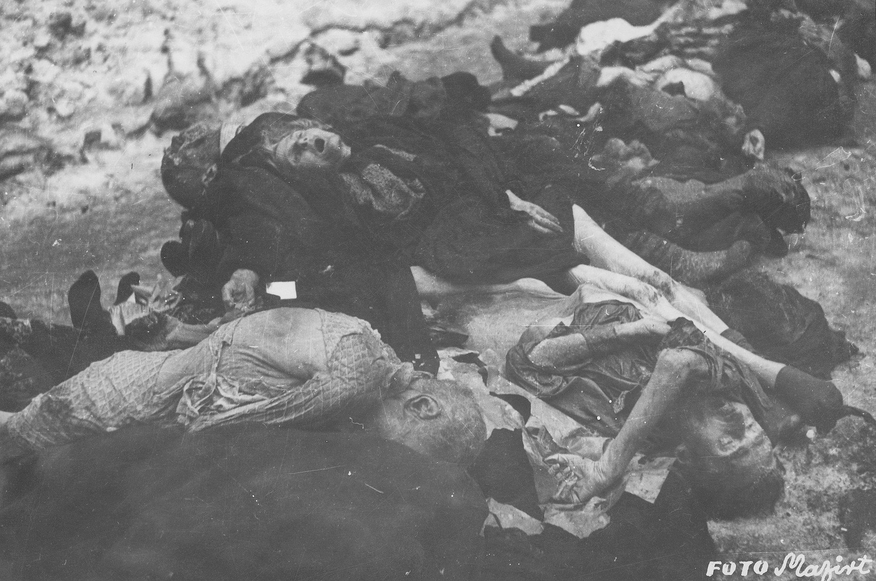"The corpses of Jews in the courtyard of the Dohany Street Synagogue.  During the last few months of the war in Hungary, the Nyilas (Arrow Cross) exploited the anarchic conditions in the areas still under their control to continue their excesses against the Jews.  This was particularly true in Budapest, despite the fact that the Soviet army had completely encircled the city by December 27, 1944.  The reign of terror that had begun with Szalaszi's assumption of power on October 15, 1944, went almost completely unchecked after the beginning of the Soviet siege on December 9.  Gangs of armed Nyilas--mostly teenagers--roamed the city hunting for Jews in hiding.  They searched them out in hospitals, shelters, homes outside the ghetto, in the International Ghetto, and in the large ghetto.  After robbing the Jews of their remaining valuables, the Nyilas shot them on the spot or marched them to the banks of the Danube, where they shot them, and threw their bodies into the river.  A large number of Jews who were murdered in the ghetto were buried in mass graves in the courtyard of the Dohany Street Synagogue.  The most horrific of these attacks occurred on the Pest side of the capital, at the two Jewish hospitals located on Maros and Varosmajor streets.  The Maros Street hospital, which had operated under the protection of the International Red Cross during the German occupation, was attacked on January 11, 1945.  After the initial melee, during which Nyilas gang members wantonly destroyed hospital equipment, threw patients out of their beds and trampled them, and murdered staff members, survivors were ordered to dig a mass grave, remove and bury the bodies.  They were then shot and buried in the grave themselves.  Only one nurse survived of the 92 people that were in the hospital at the time.  Three days later, on January 14, the hospital on Varosmajor Street was attacked, resulting in the deaths of 150 patients and medical staff.  These manhunts and massacres continued unabated until the liberation of Budapest in April.  [R. Braham, ""The Politics of Genocide,"" vol. 2: 995-1007]"