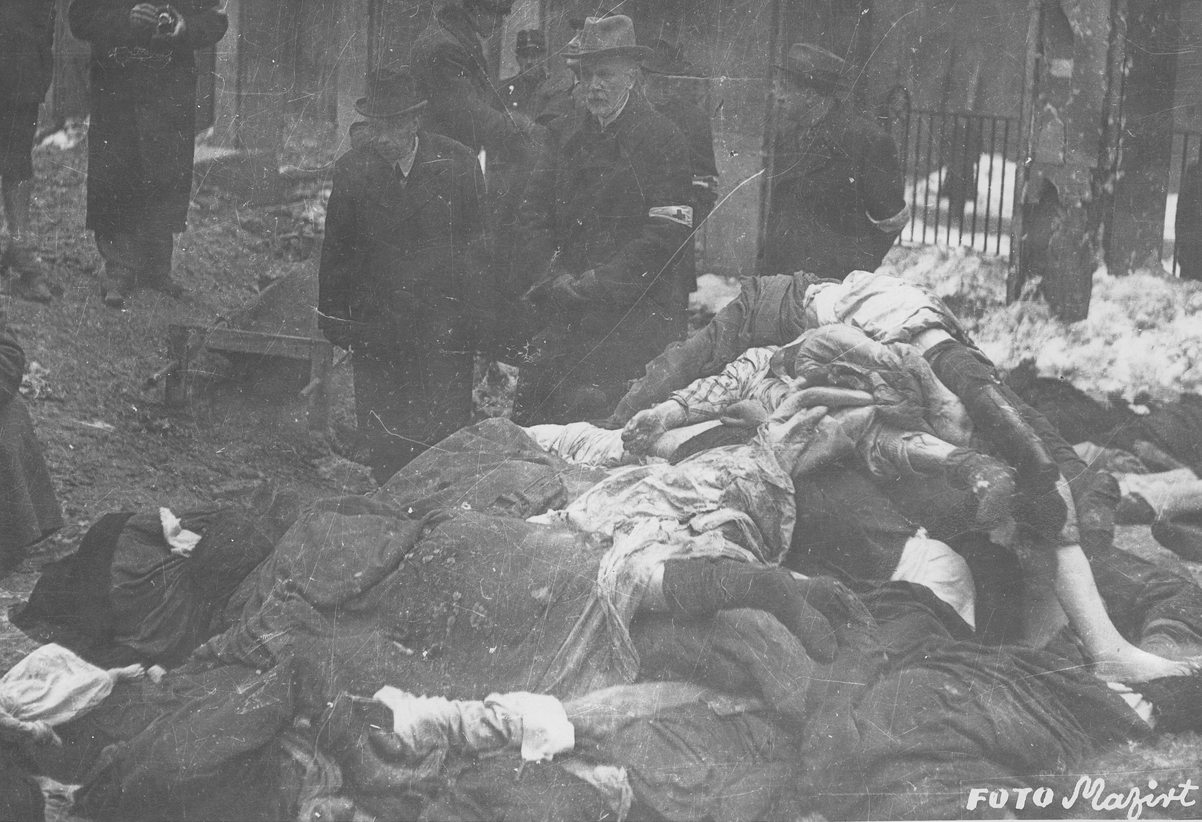 Members of the Commission for the Investigation of Nazi and Arrow Cross Atrocities examine the bodies of Jews in the courtyard of the Dohany Street Synagogue.  During the last few months of the war in Hungary, the Nyilas (Arrow Cross) exploited the anarchic conditions in the areas still under their control to continue their excesses against the Jews.  This was particularly true in Budapest, despite the fact that the Soviet army had completely encircled the city by December 27, 1944.  The reign of terror that had begun with Szalaszi's assumption of power on October 15, 1944, went almost completely unchecked after the beginning of the Soviet siege on December 9.  Gangs of armed Nyilas--mostly teenagers--roamed the city hunting for Jews in hiding.  They searched them out in hospitals, shelters, homes outside the ghetto, in the International Ghetto, and in the large ghetto.  After robbing the Jews of their remaining valuables, the Nyilas shot them on the spot or marched them to the banks of the Danube, where they shot them, and threw their bodies into the river.  A large number of Jews who were murdered in the ghetto were buried in mass graves in the courtyard of the Dohany Street Synagogue.  The most horrific of these attacks occurred on the Pest side of the capital, at the two Jewish hospitals located on Maros and Varosmajor streets.  The Maros Street hospital, which had operated under the protection of the International Red Cross during the German occupation, was attacked on January 11, 1945.  After the initial melee, during which Nyilas gang members wantonly destroyed hospital equipment, threw patients out of their beds and trampled them, and murdered staff members, survivors were ordered to dig a mass grave, remove and bury the bodies.  They were then shot and buried in the grave themselves.  Only one nurse survived of the 92 people that were in the hospital at the time.  Three days later, on January 14, the hospital on Varosmajor Street was attacked, resulting in 