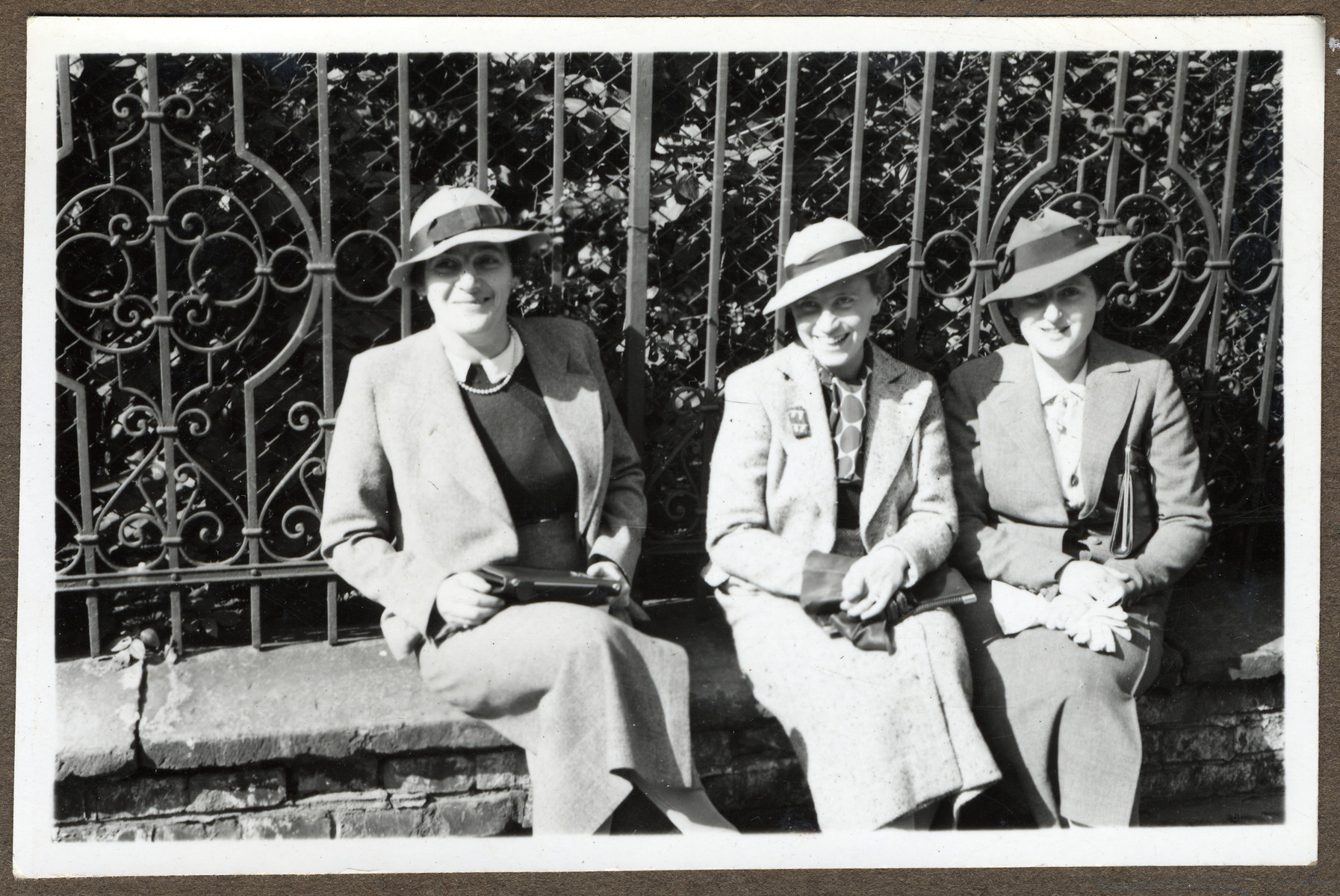 Three Czech  women of Jewish origin sit together on a ledge in front of a metal fence in Nachod.  Pictured are Zofie Polakova, Lola Krausova and Zdenka Beckova.