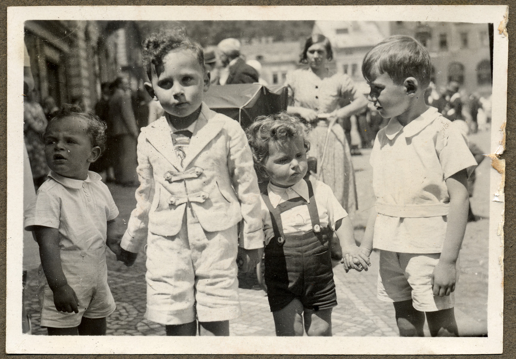 Four young children of Jewish origin participate in the town's celebration of the feast of Corpus Christi on the main square in Nachod.  Pictured from left to right are Tommy Beck, son of Rudolf and Vilma Beck who perished in Birkenau; Michal Kraus;  Max Michael Goldschmid who survived the war in Palestine and Ivan Polak, who perished in Dachau.