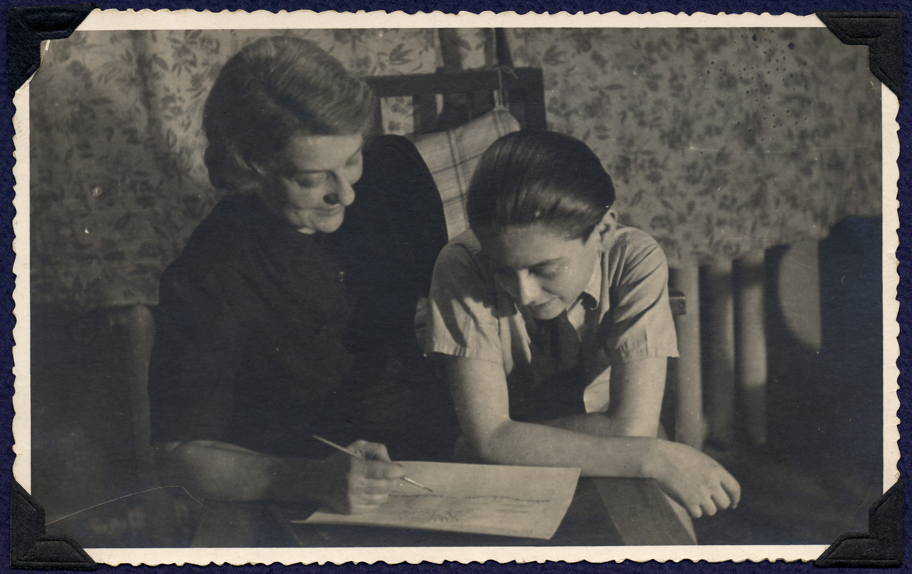 A mother and son, both survivors of Theresienstadt, study a document in their apartment in postwar Prague.  Pictured are Margaret and Michael Grunbaum.