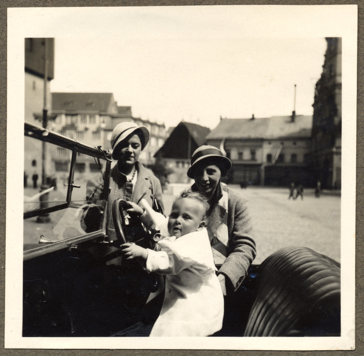 A young mother and her friend look on as her baby son pretends to drive their automobile in the main square of Nachod.    Pictured are Lotte Kraus (right) and her son Michal.  On the left is Hela Hancl who was half-Jewish and married to a non-Jew and therefore spared deportation.