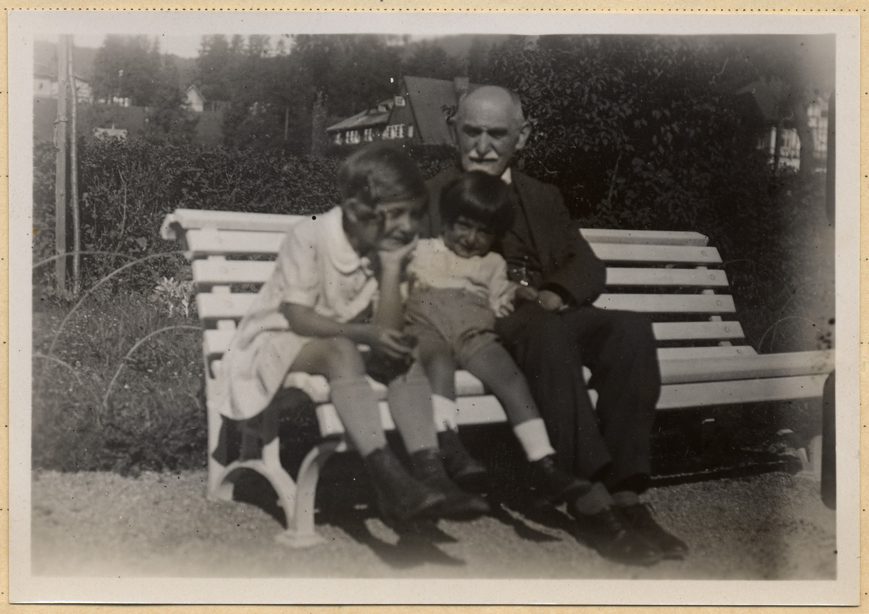 A grandfather sits next to his two grandchildren on a park bench.  Pictured are Marietta, Michael and Eduard Grunbaum.