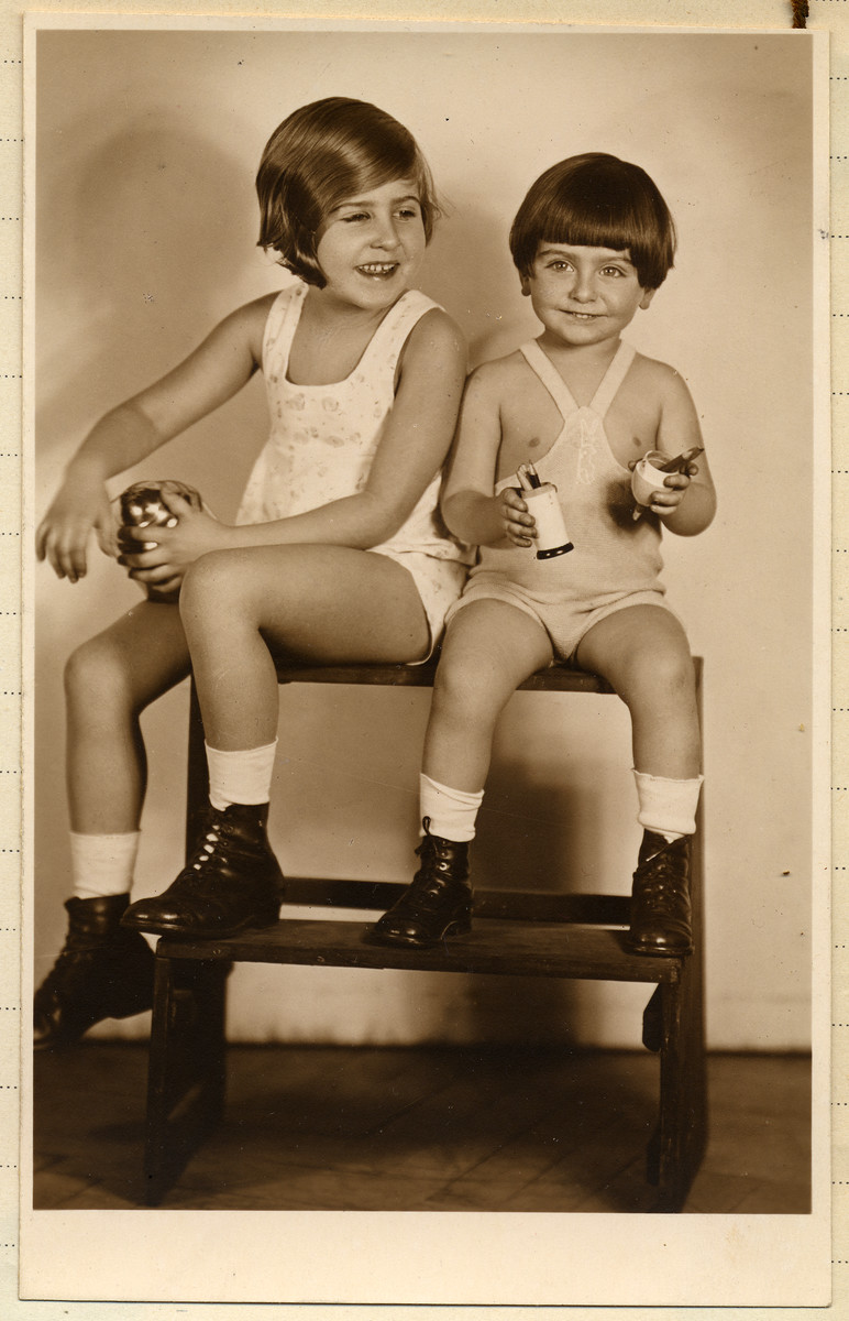 Studio portrait of two Czech-Jewish siblings sitting on a step-stool.  Pictured are Marietta and Michael Grunbaum.