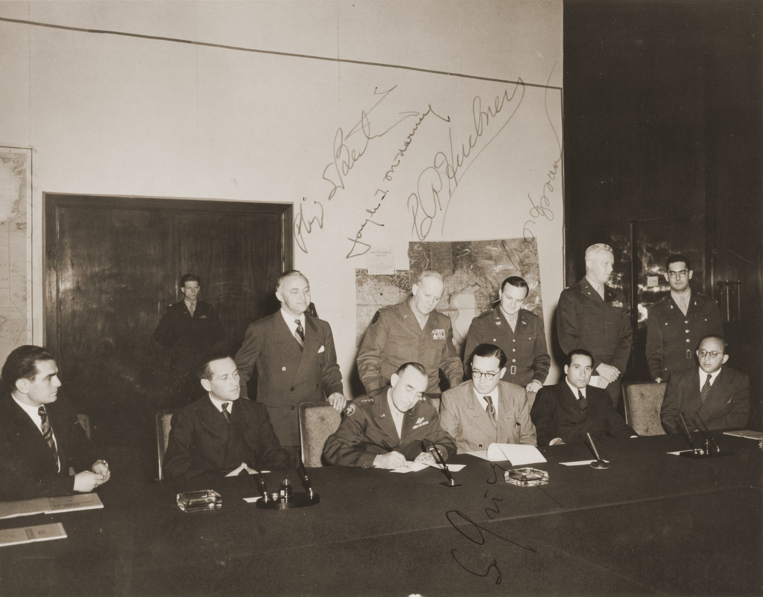 General Joseph McNarney signs the charter of recognition of the Central Committee of Liberated Jews in Bavaria, whereby the American Army acknowledged the Central Committee as the official representative body of Jewish DPs in the American Zone of Germany.  Pictured standing in the back row, from left to right, are: Rabbi Philip Bernstein; General Clarence Huebner; Abraham Hyman; Colonel George Scithers; Rabbi Herbert Friedman.  Seated at the table, from left to right, are: Leon Retter (Aryeh Nesher); unknown; General Joseph McNarney; Samuel Gringauz; unknown; and Boris Pliskin.