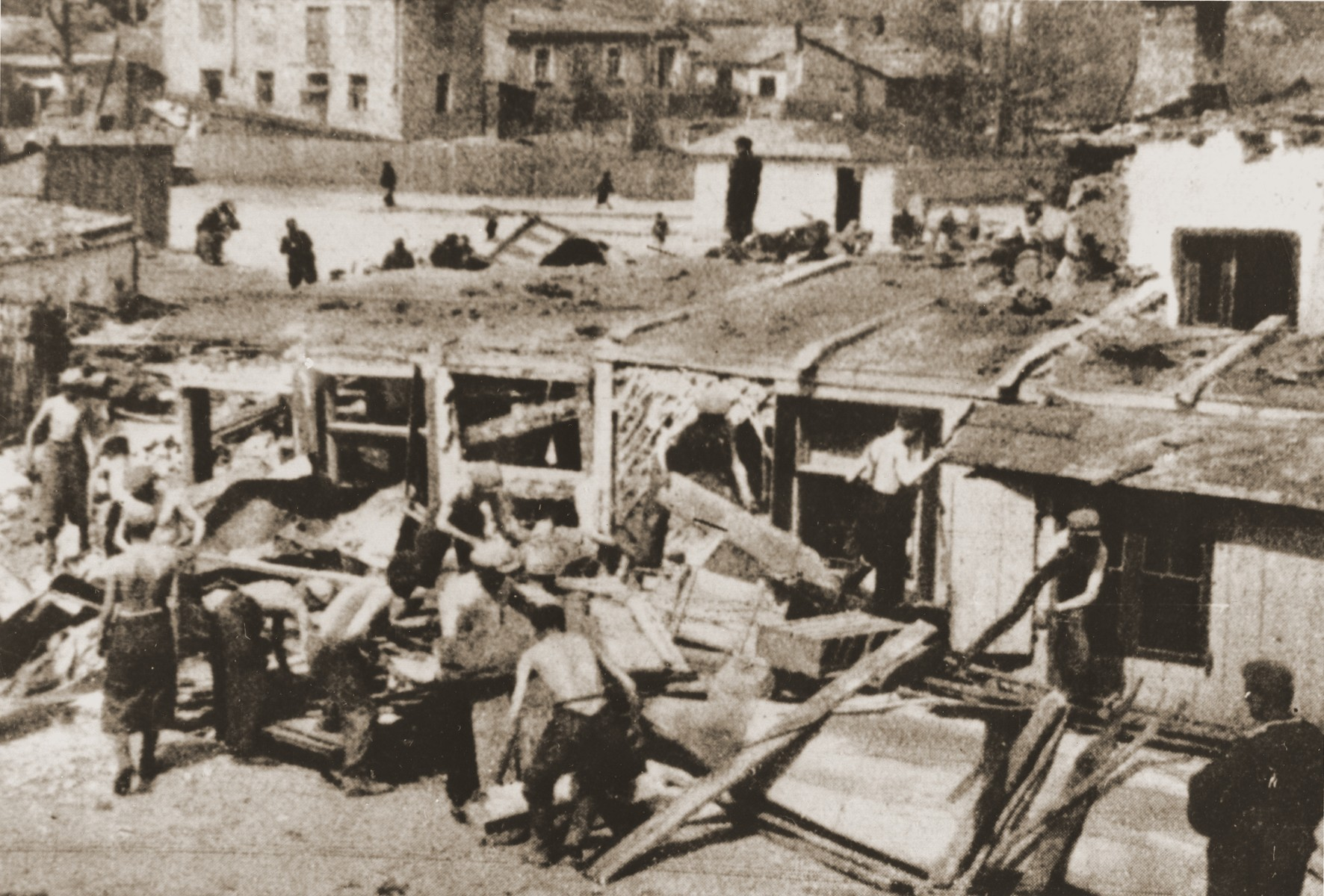 Polish laborers cart away furniture and dismantle buildings after the liquidation of the Lublin ghetto.