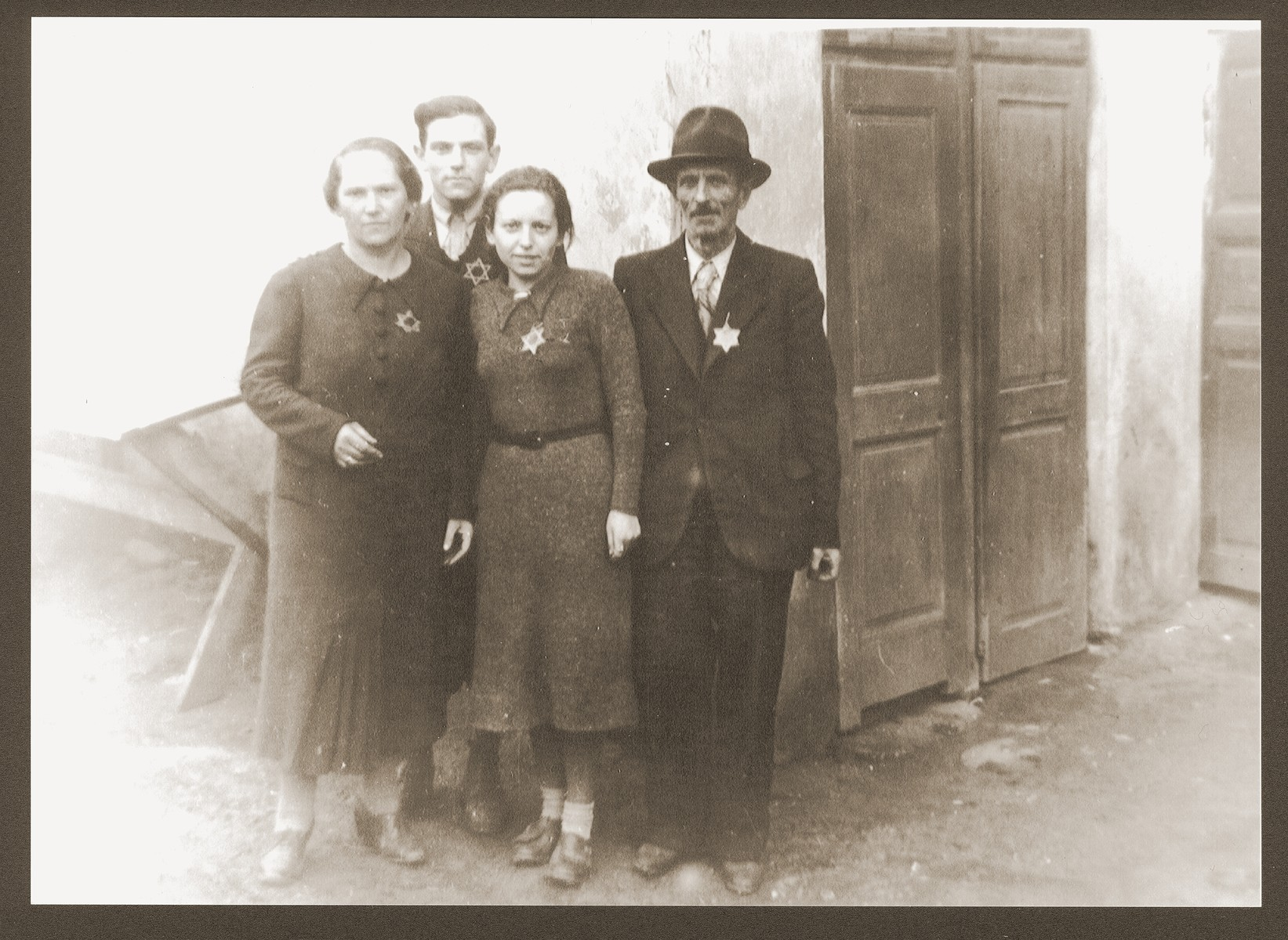Portrait of the Weidenfeld family wearing Jewish badges in the Czernowitz (Cernauti) ghetto shortly before their deportation to Transnistria.  Pictured from left to right are Yetty, Meshulem-Ber, Sallie and Simche Weidenfeld.