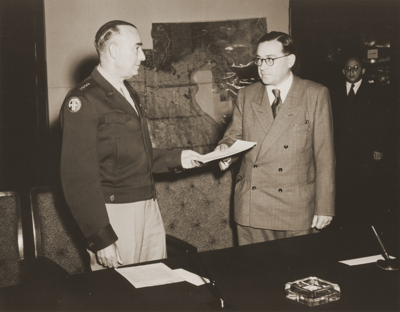 General Joseph McNarney, Commander of the American army of occupation in Germany, hands Dr. Samuel Gringauz, Chairman of the Central Committee of Liberated Jews in the U.S. Zone of Germany, the signed Charter of Recognition, whereby the American army acknowledged the Central Committee as the official representative body of Jewish DPs in the American Zone of Germany.  Pictured at the far right is Boris Pliskin.