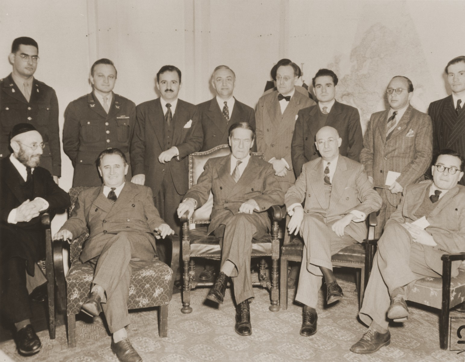 Group portrait of participants at a meeting between Jewish DP leaders and visiting American Jewish leaders in the American Zone of Germany.  Pictured in the back row, from left to right, are: Rabbi Herbert Friedman; Abraham Hyman; Isaiah Kennen; Philip Bernstein; Philip Forman; Leon Retter (Aryeh Nesher); Boris Pliskin; Rabbi Gerhard Rose. In the front row from left to right, are: Rabbi Samuel Snieg; Nahum Goldmann; Rabbi Stephen Wise; Jacob Blaustein; and Samuel Gringauz.