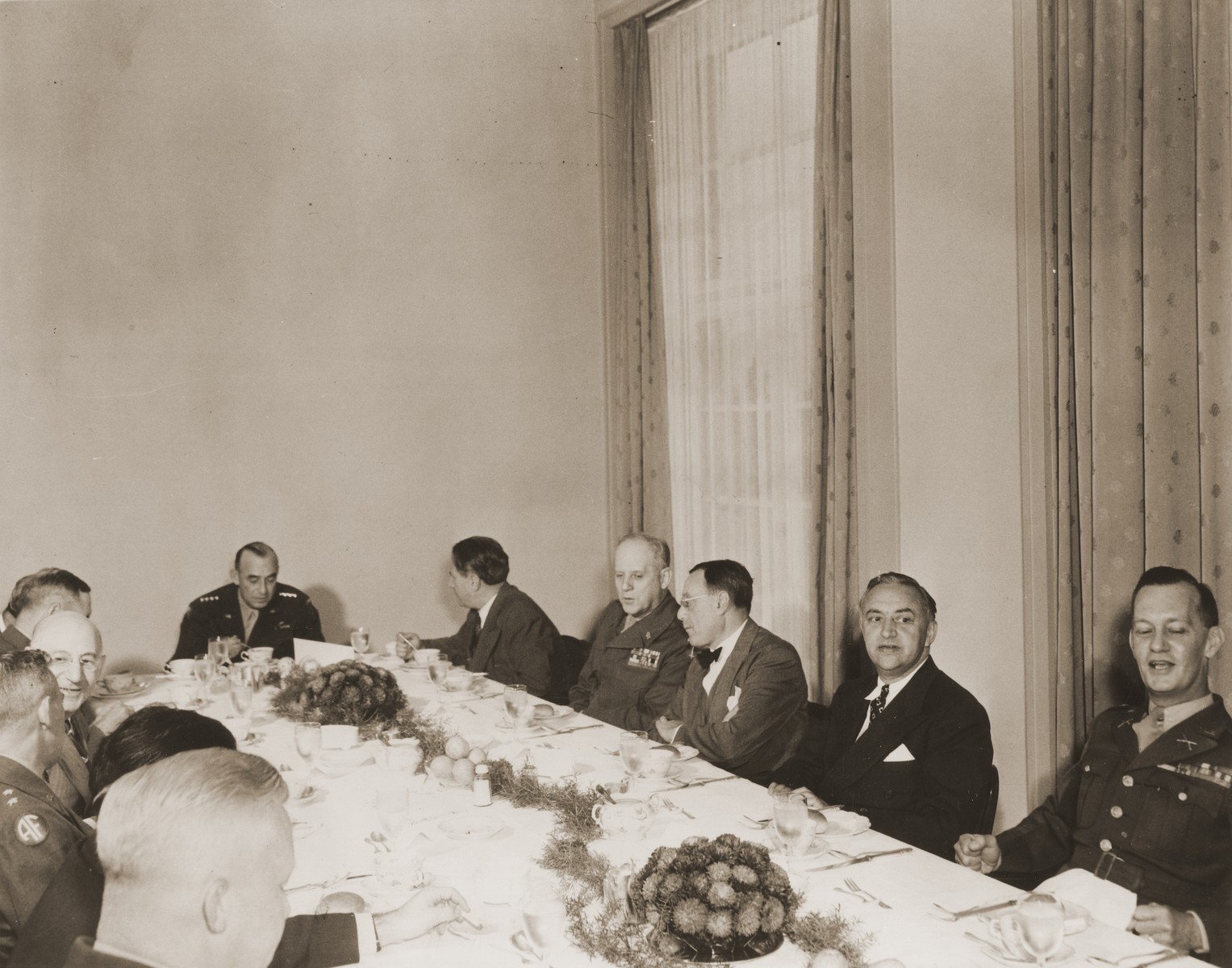 Visiting American Jewish leaders meet over dinner with the commanders of the American army of occupation in Germany.  The meeting took place at military headquarters located in the former I.G. Farben facility in Frankfurt am Main.  Pictured counter-clockwise from the right are: unknown; Rabbi Phillip Bernstein; Philip Forman; General Clarence Huebner; Nahum Goldmann; General Joseph McNarney; Rabbi Stephen Wise; unknown; Jacob Blaustein; unknown; unknown; and Colonel George Scithers.