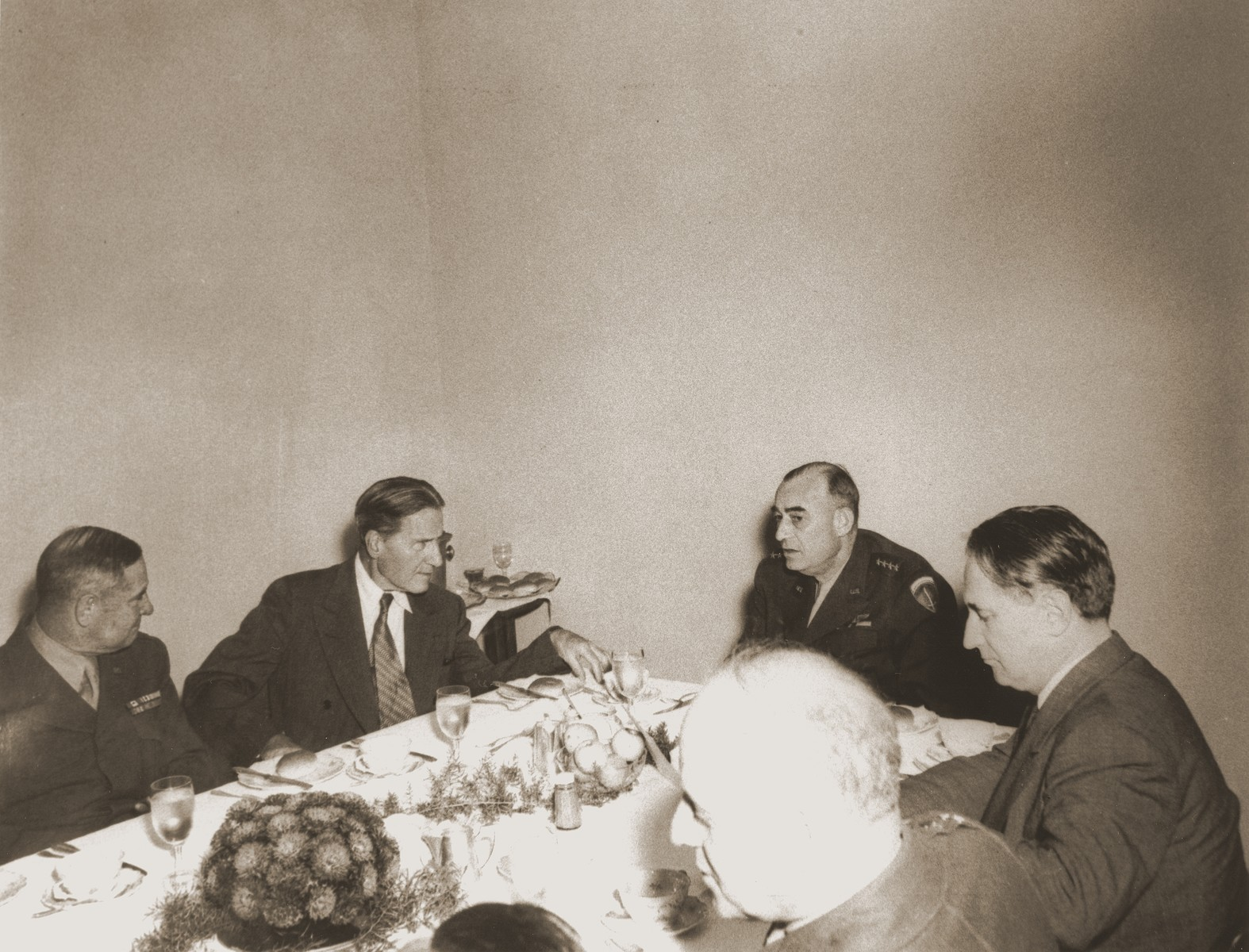 Visiting American Jewish leaders meet over dinner with the commanders of the American Army of Occupation in Germany.  The meeting took place at military headquarters located in the former I.G. Farben facility in Frankfurt am Main.  Pictured clockwise from the left are: unknown; Rabbi Stephen Wise; General Joseph McNarney; Nahum Goldmann; and General Clarence Huebner.