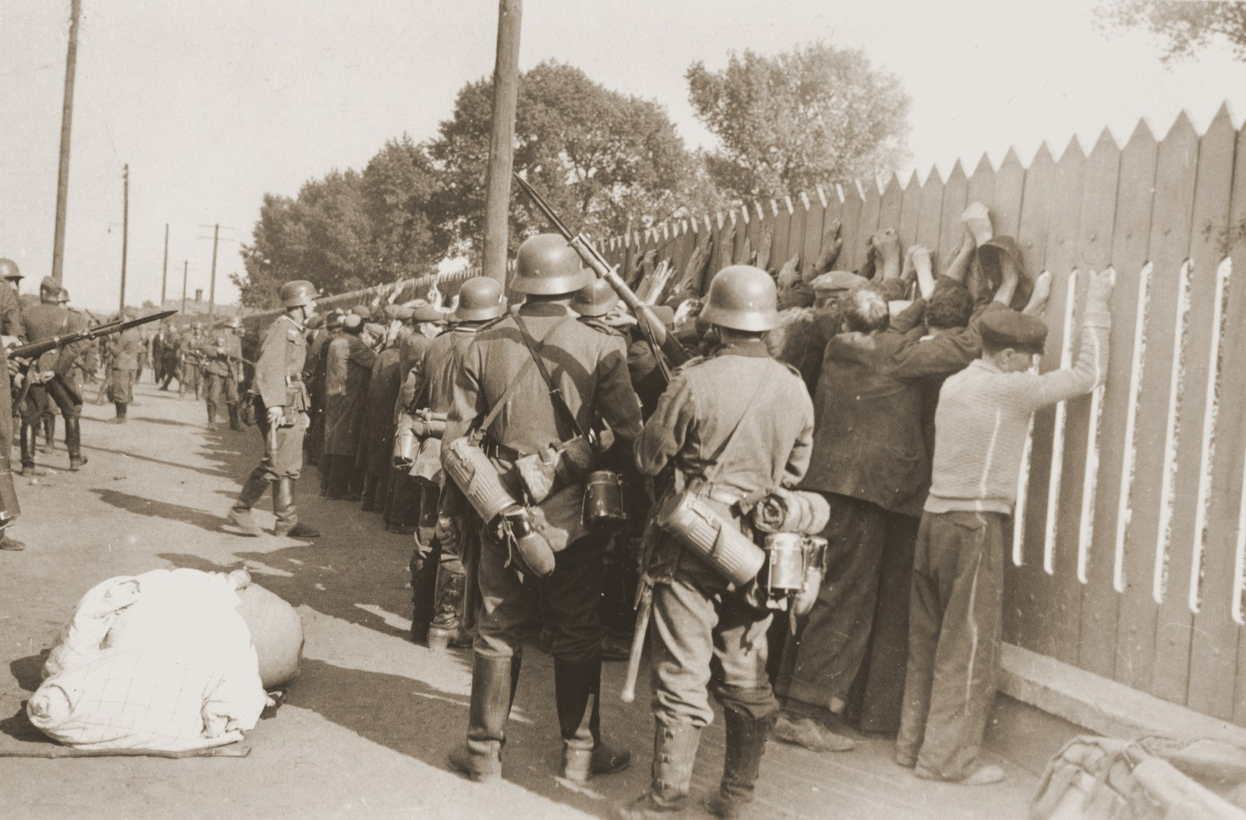 German soldiers round-up a group of Jewish men and line them up against a picket fence in Czestochowa.  One photograph from an album belonging to a member of a Wehrmacht machine gunners' unit, which was found after the war by Lorenzo Hawkins (the donor's grandfather), an American serviceman in Company B, 56th Armored Engineer Battalion.