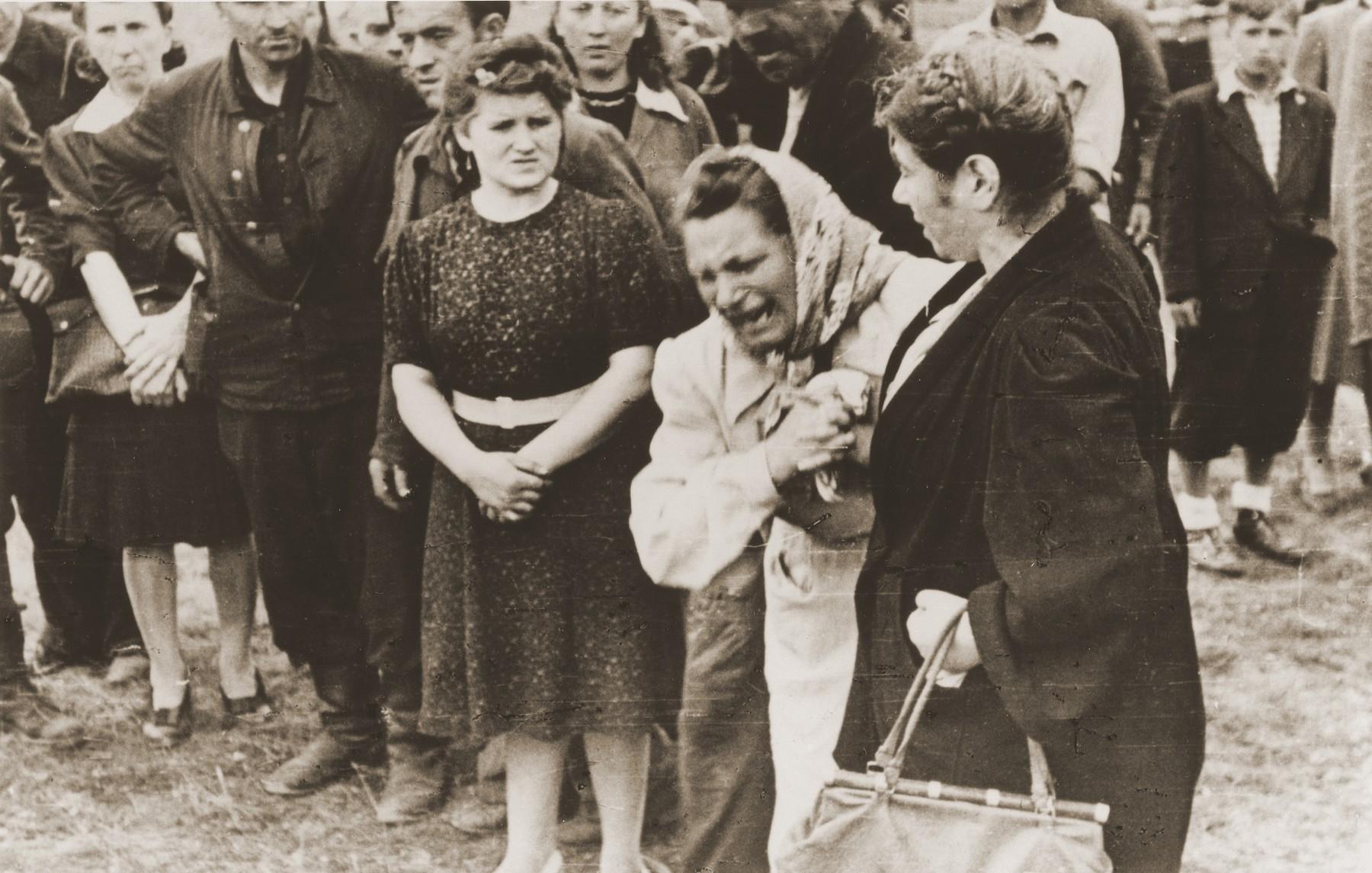 A woman cries in grief for the loss of her husband and other victims of the Kielce pogrom during the public burial.