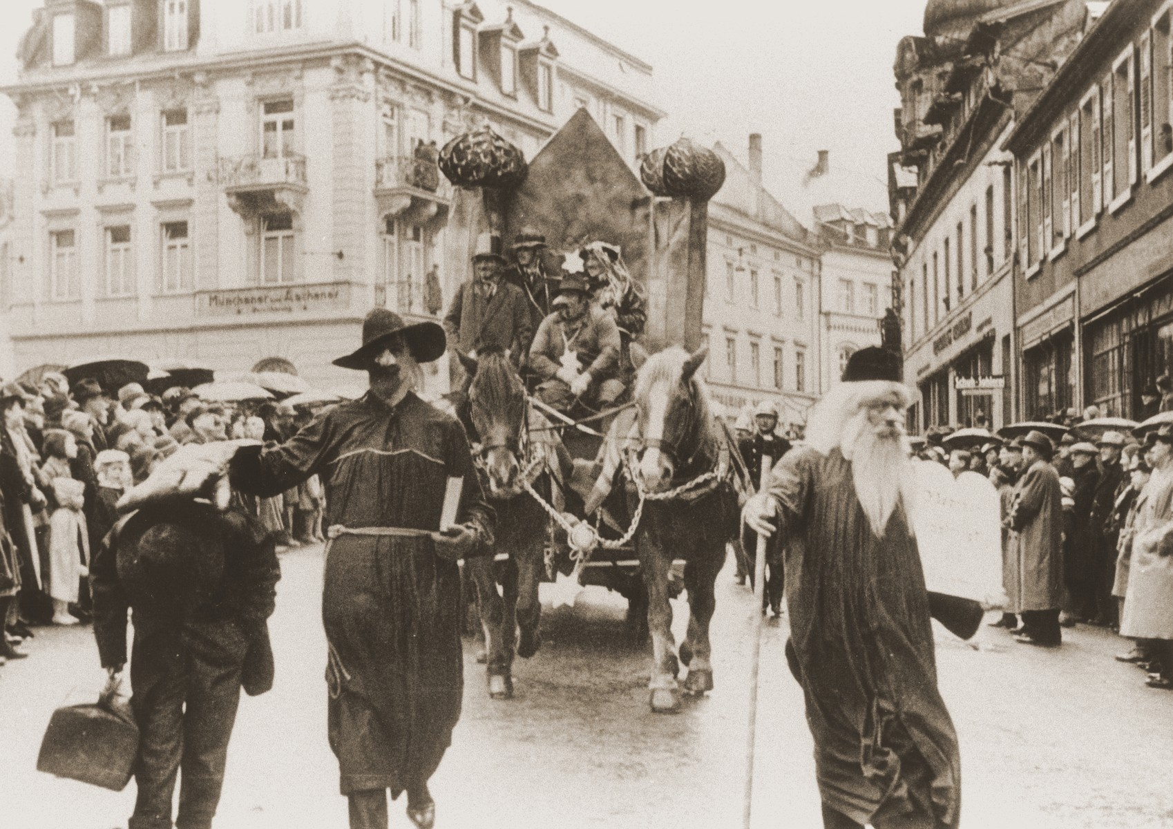 A troupe of actors in a carnival parade parodies Jewish life in Germany.  The float features a mock-up of a burning synagogue.