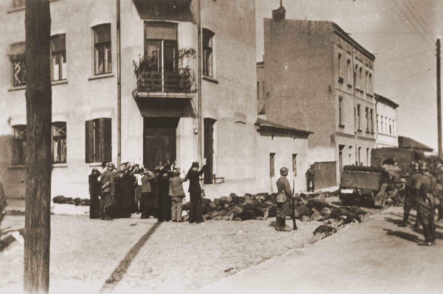 A group of Jewish men, who have been rounded-up by German soldiers, await execution on a street in Czestochowa.  In front of them lie the corpses of those who were shot earlier.  One photograph from an album belonging to a member of a Wehrmacht machine gunners' unit, which was found after the war by Lorenzo Hawkins (the donor's grandfather), an American serviceman in Company B, 56th Armored Engineer Battalion.