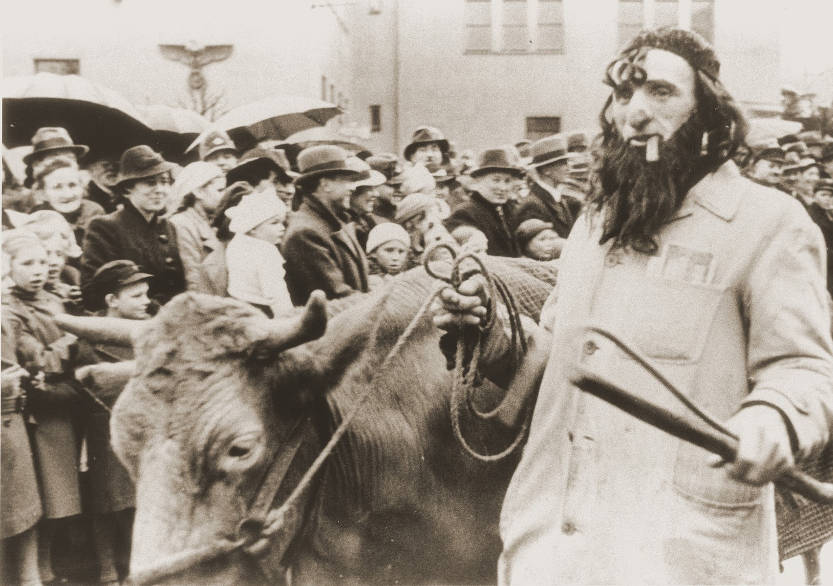 A troupe of actors in a carnival parade parodies Jewish life in Germany.  One of the actors is dressed up as a Jewish cattle dealer, who carries a wad of money in his coat pocket.