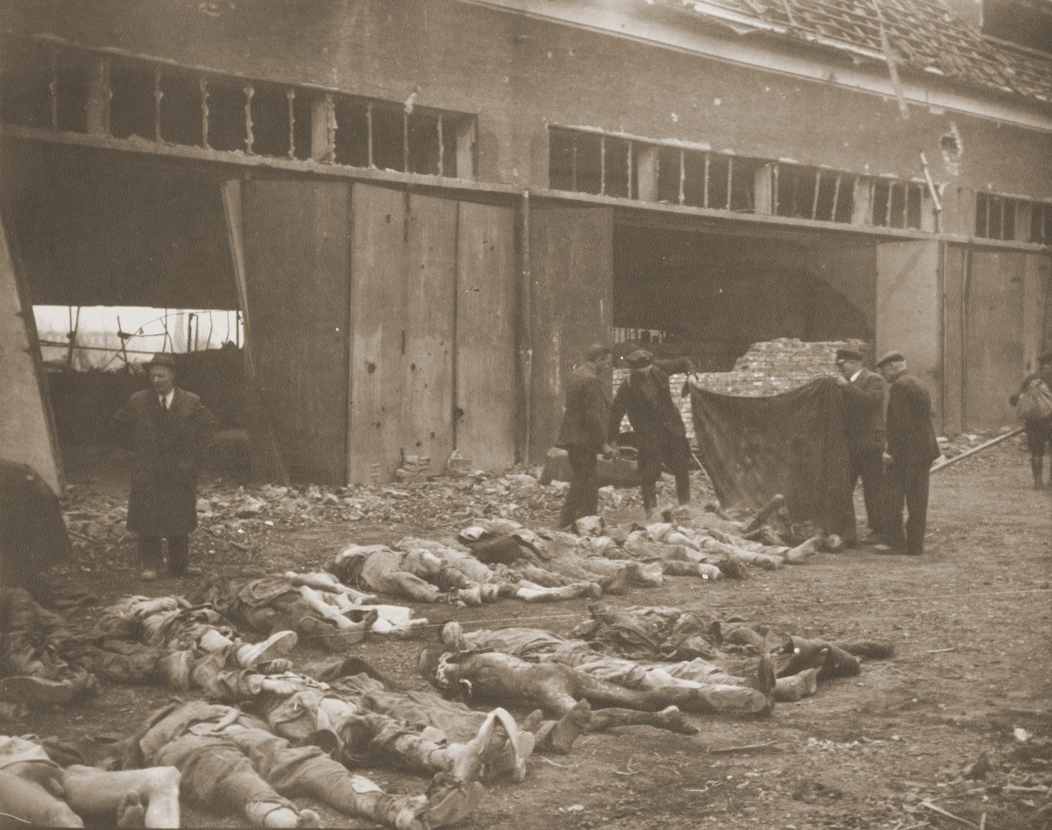 German civilians cover the bodies of prisoners killed in the Nordhausen concentration camp.  The corpses have been laid out in long rows outside the central barracks (Boelke Kaserne).