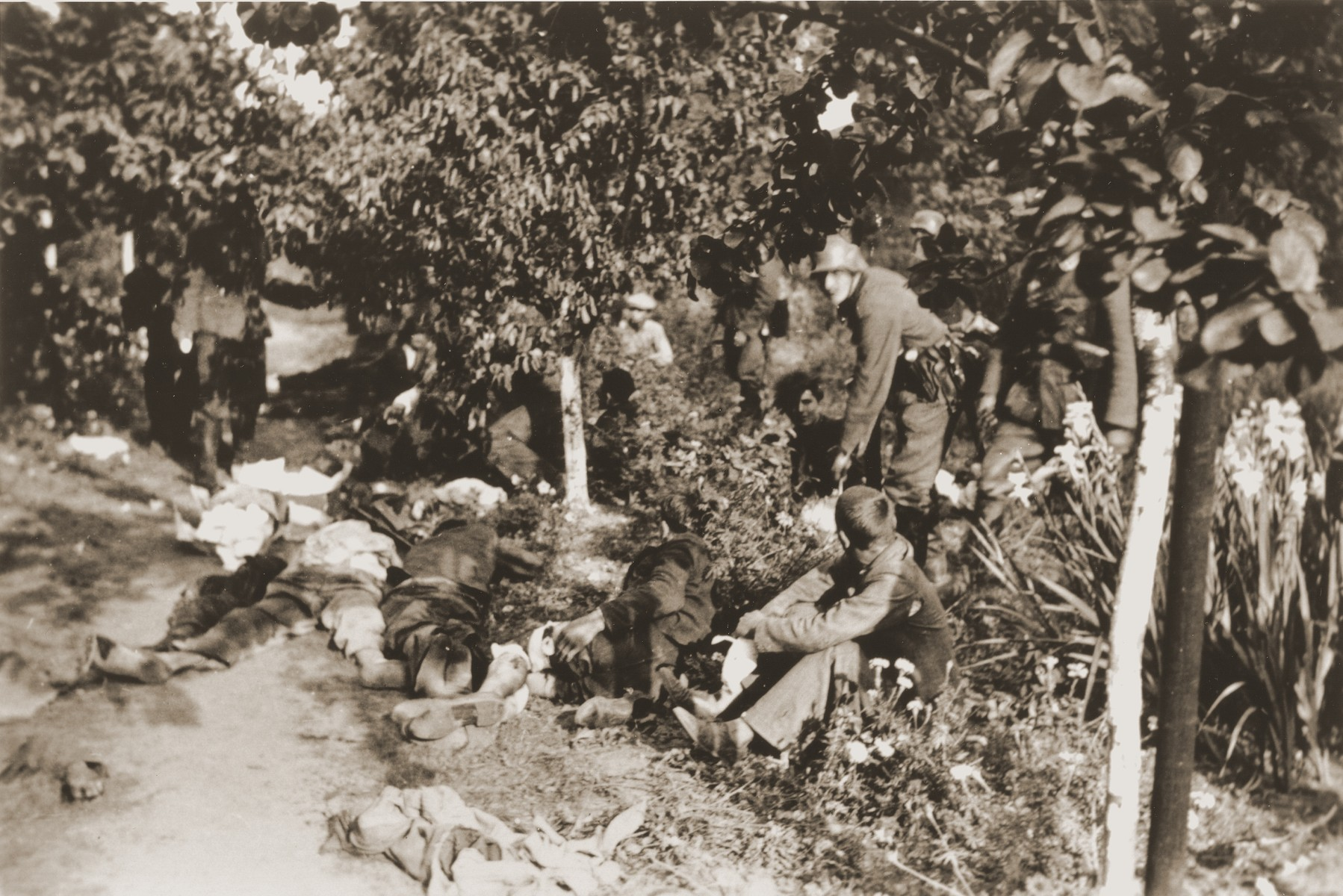 A young man, sitting among the bodies of murdered civilians in a park-like setting, has his head turned toward the German soldier standing over him.   One photograph from an album belonging to a member of a Wehrmacht machine gunners' unit, which was found after the war by Lorenzo Hawkins (the donor's grandfather), an American serviceman in Company B, 56th Armored Engineer Battalion.