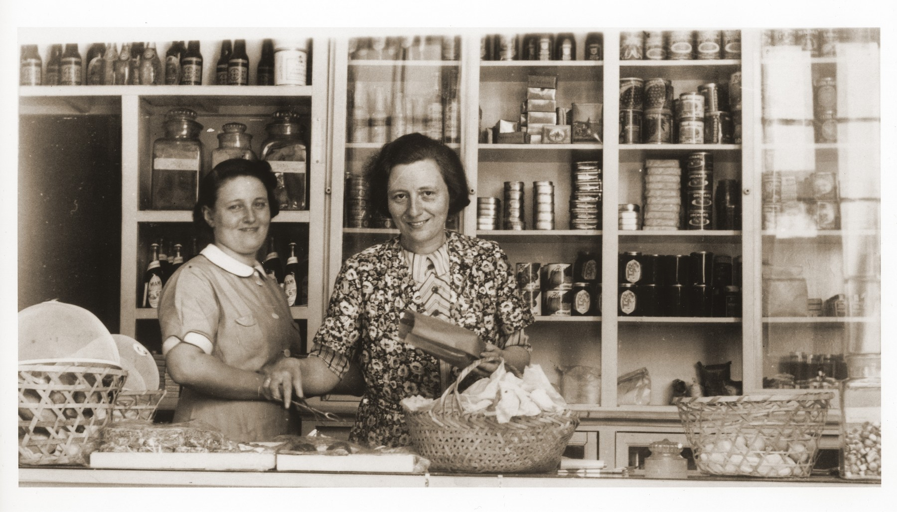 Two German Jewish refugee women stand behind the counter of the Elite Provision Store (delicatessen) in Shanghai.  Pictured on the left is the owner, Gerda Harpuder; on the right is her cousin Kate Benjamin.