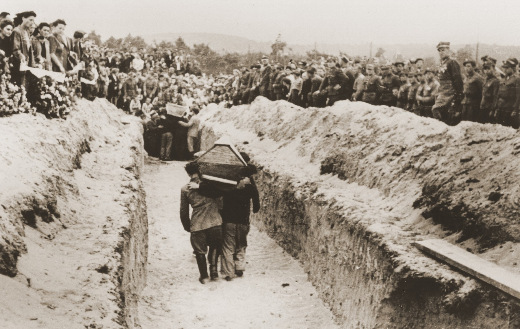 Pallbearers carrying the victims of the Kielce pogrom, place the coffins in a mass grave at the Jewish cemetery.