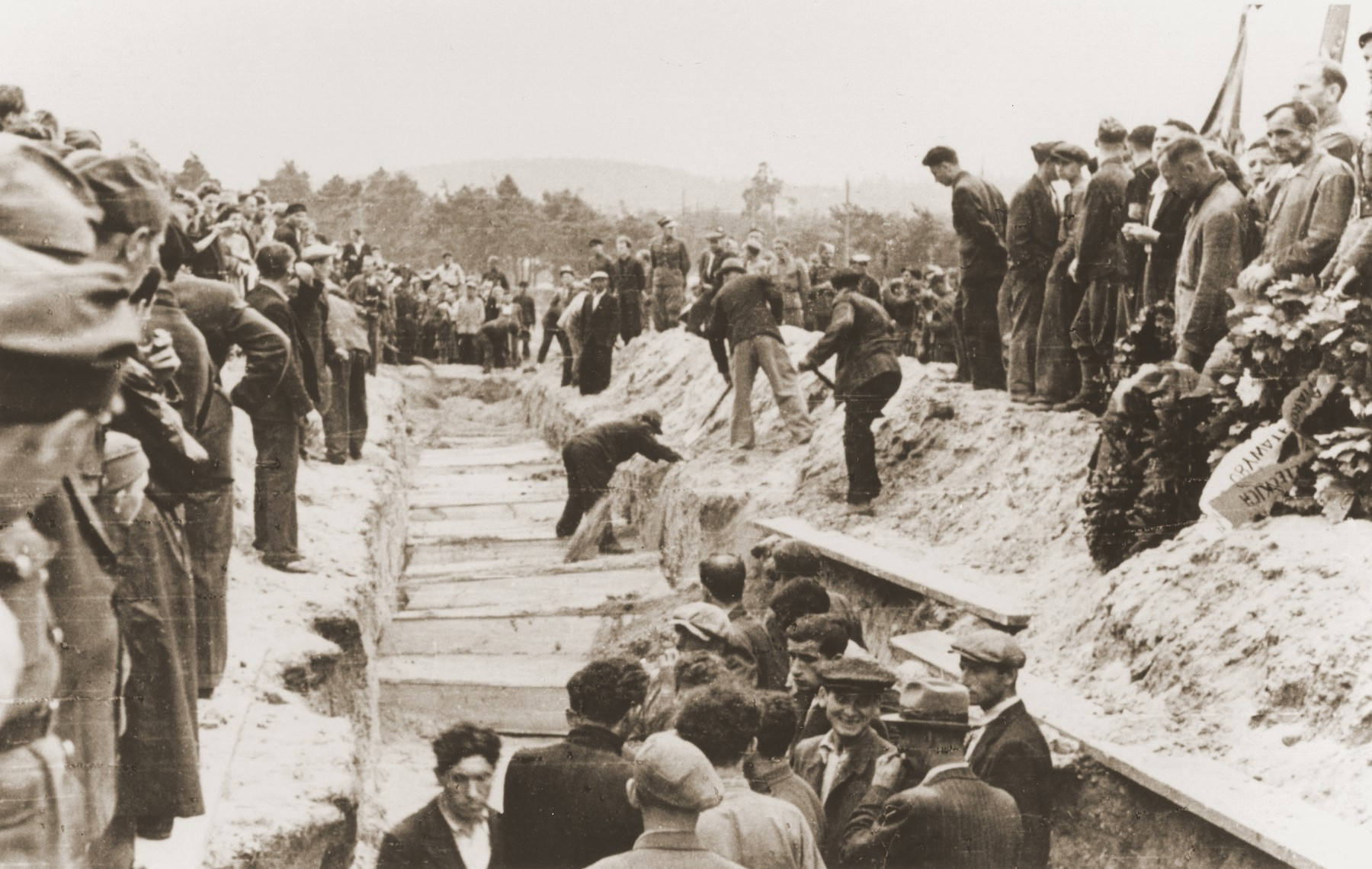 Mourners and local residents watch as men shovel dirt into the mass grave of the victims of the Kielce pogrom.