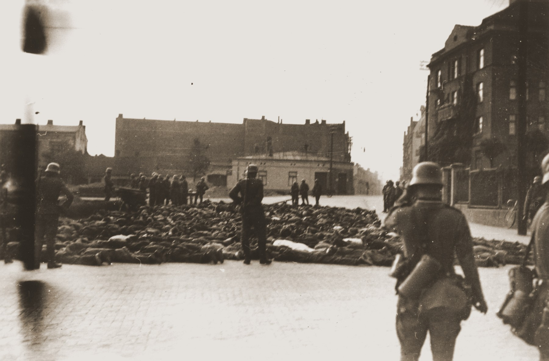 German soldiers patrol a public square in Czestochowa, where the bodies of those they shot have been collected.  One photograph from an album belonging to a member of a Wehrmacht machine gunners' unit, which was found after the war by Lorenzo Hawkins (the donor's grandfather), an American serviceman in Company B, 56th Armored Engineer Battalion.