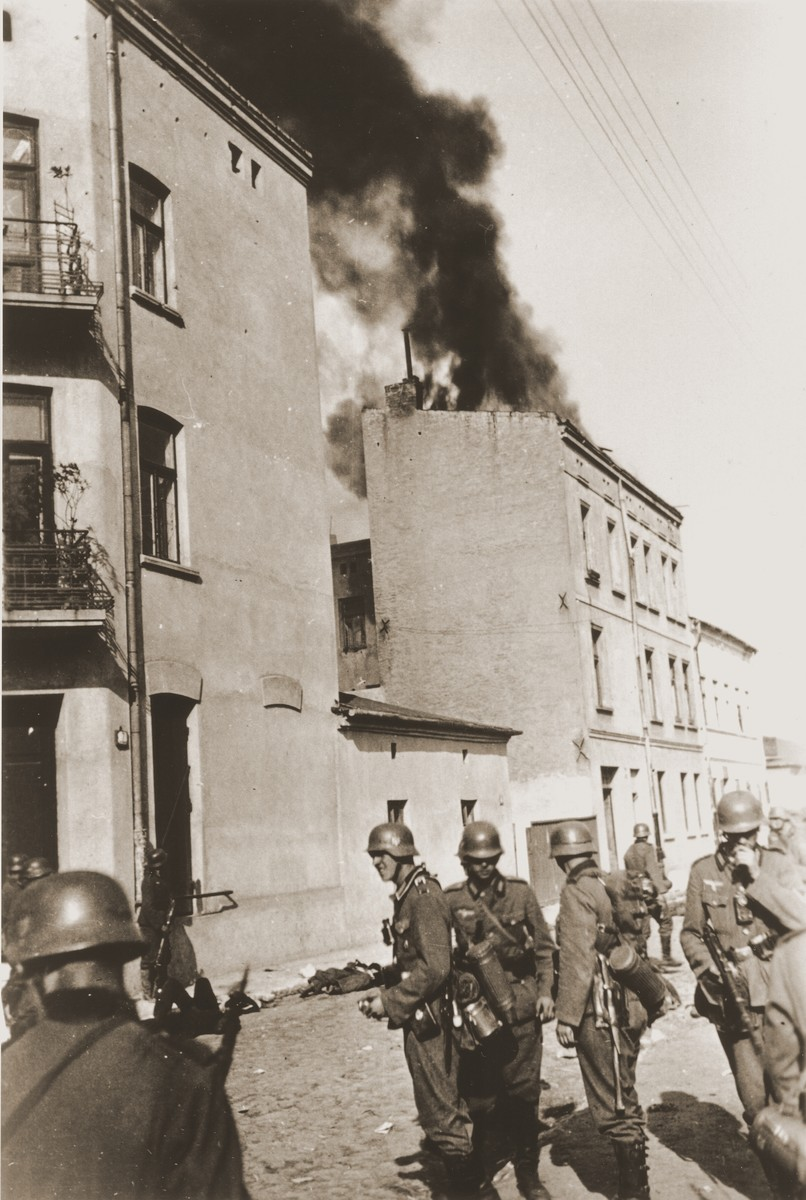 German soldiers stand guard on a street in Czestochowa, where dead bodies lie strewn along the pavement.  In the background smoke rises from a burning building.   One photograph from an album belonging to a member of a Wehrmacht machine gunners' unit, which was found after the war by Lorenzo Hawkins (the donor's grandfather), an American serviceman in Company B, 56th Armored Engineer Battalion.