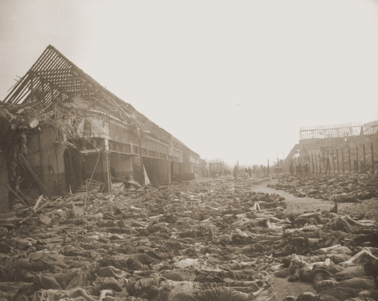 View of the main street of the Nordhausen concentration camp, outside of the central barracks (Boelke Kaserne), where the bodies of prisoners have been laid out in long rows.