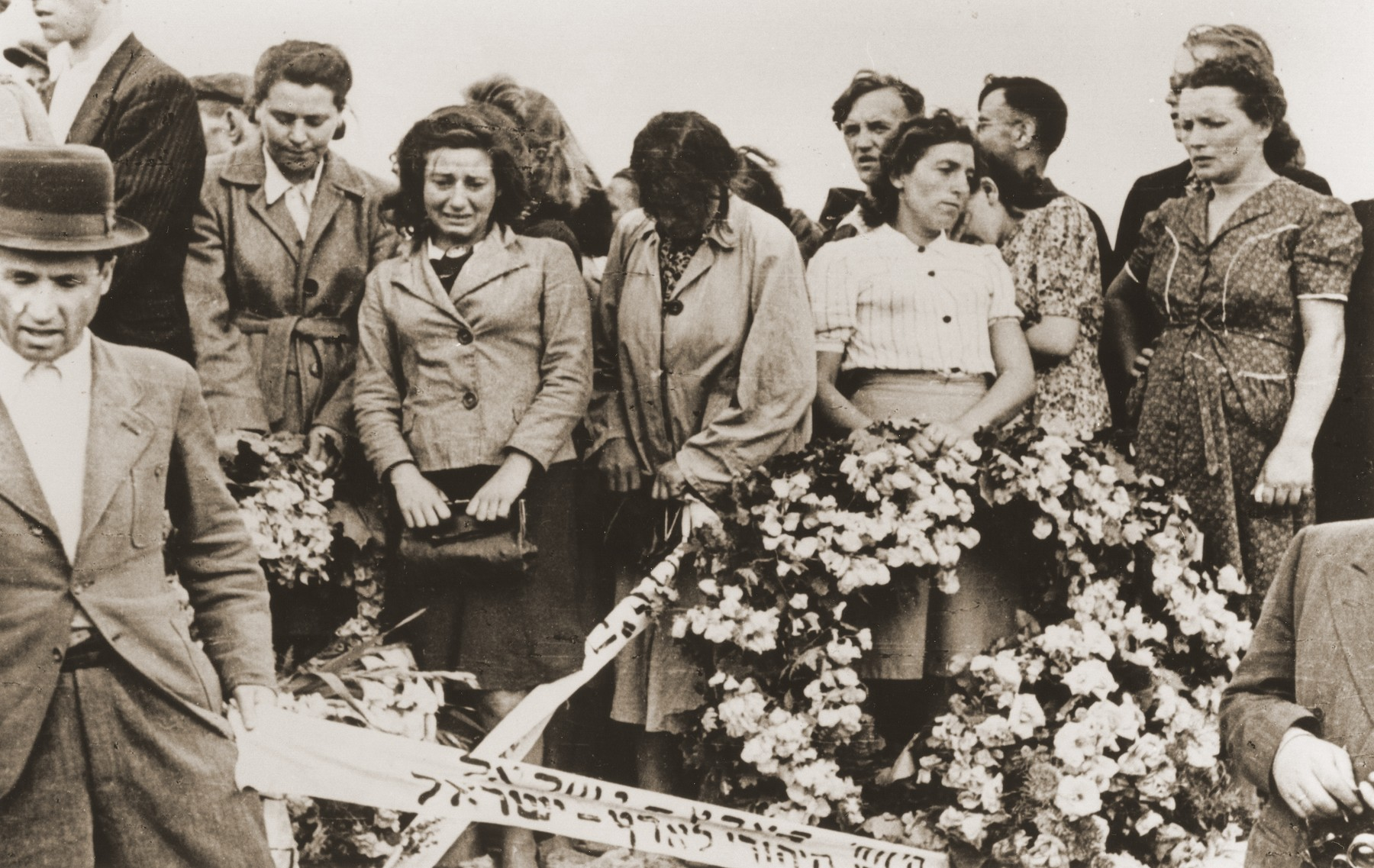 Mourners bearing wreaths and banners grieve at the funeral of the Kielce pogrom victims.