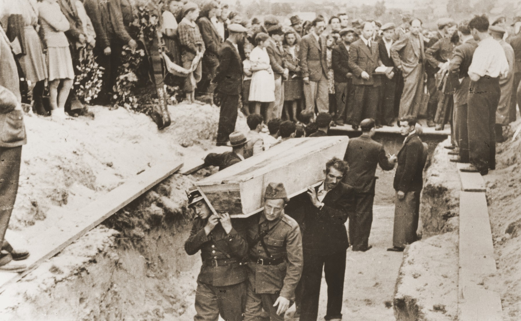 Pallbearers, some of whom are Polish soldiers, place the coffins of the victims of the Kielce pogrom in a mass grave at the Jewish cemetery.