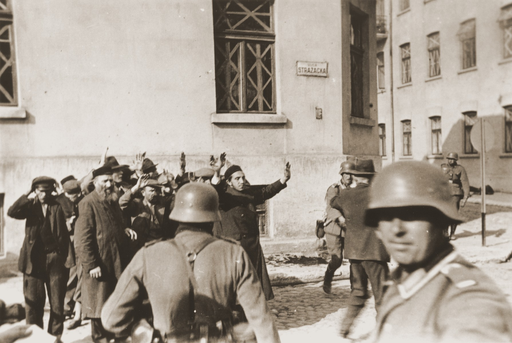 German soldiers round-up a group of Jewish men on Strazacka Street in Czestochowa.  One photograph from an album belonging to a member of a Wehrmacht machine gunners' unit, which was found after the war by Lorenzo Hawkins (the donor's grandfather), an American serviceman in Company B, 56th Armored Engineer Battalion.