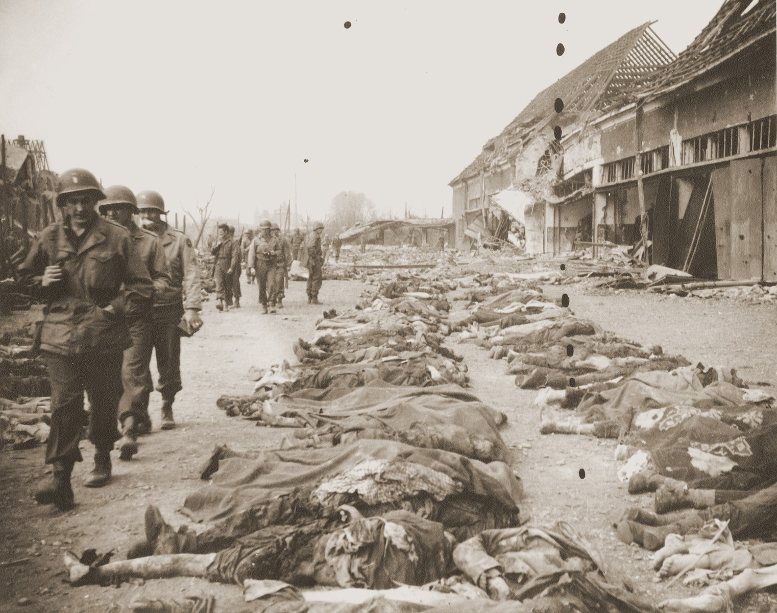 American soldiers file past the bodies of prisoners killed in the Nordhausen concentration camp, which have been laid out in long rows outside the central barracks (Boelke Kaserne).