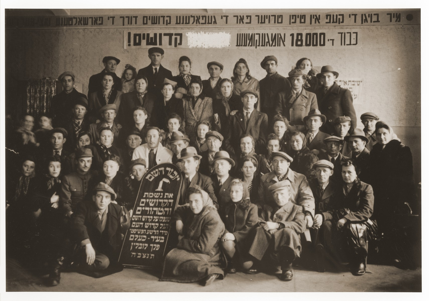Group portrait of survivors from Chelm attending a memorial reunion on the [fifth?] anniversary of the destruction of the Jewish community in Chelm.  Among those pictured is Yakov Alster (seated on far right). Also pictured is Pinchos Feldman (second row from the top, seventh from the left with a hand on his shoulder).  Pictured in the fourth row center, directly above the tablet, is Raisel Rybajzen (later Roza Munn). In the back row, far left, standing next to the tall man, is Pola (nee Engel) Munn.