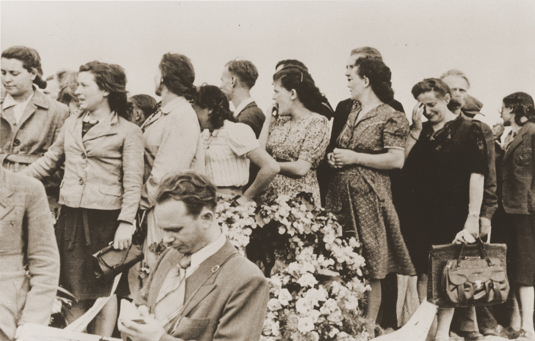 Mourners bearing a wreath, grieve at the funeral of the victims of the Kielce pogrom.  Pictured (forth from the right) is Chana Alpert.