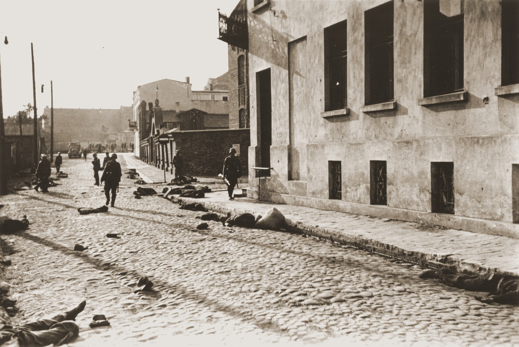 German soldiers patrol a street in Czestochowa, where dead bodies lie strewn along the pavement.    One photograph from an album belonging to a member of a Wehrmacht machine gunners' unit, which was found after the war by Lorenzo Hawkins (the donor's grandfather), an American serviceman in Company B, 56th Armored Engineer Battalion.