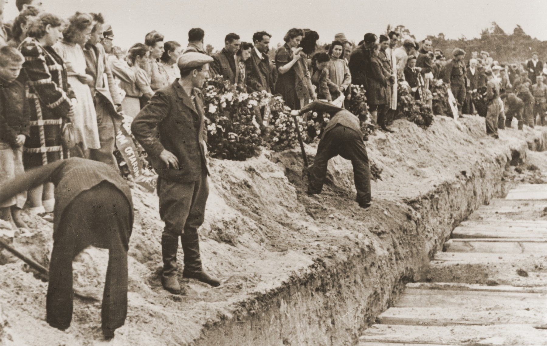 Mourners and local residents shovel dirt into the mass grave of the victims of the Kielce pogrom during the public burial.