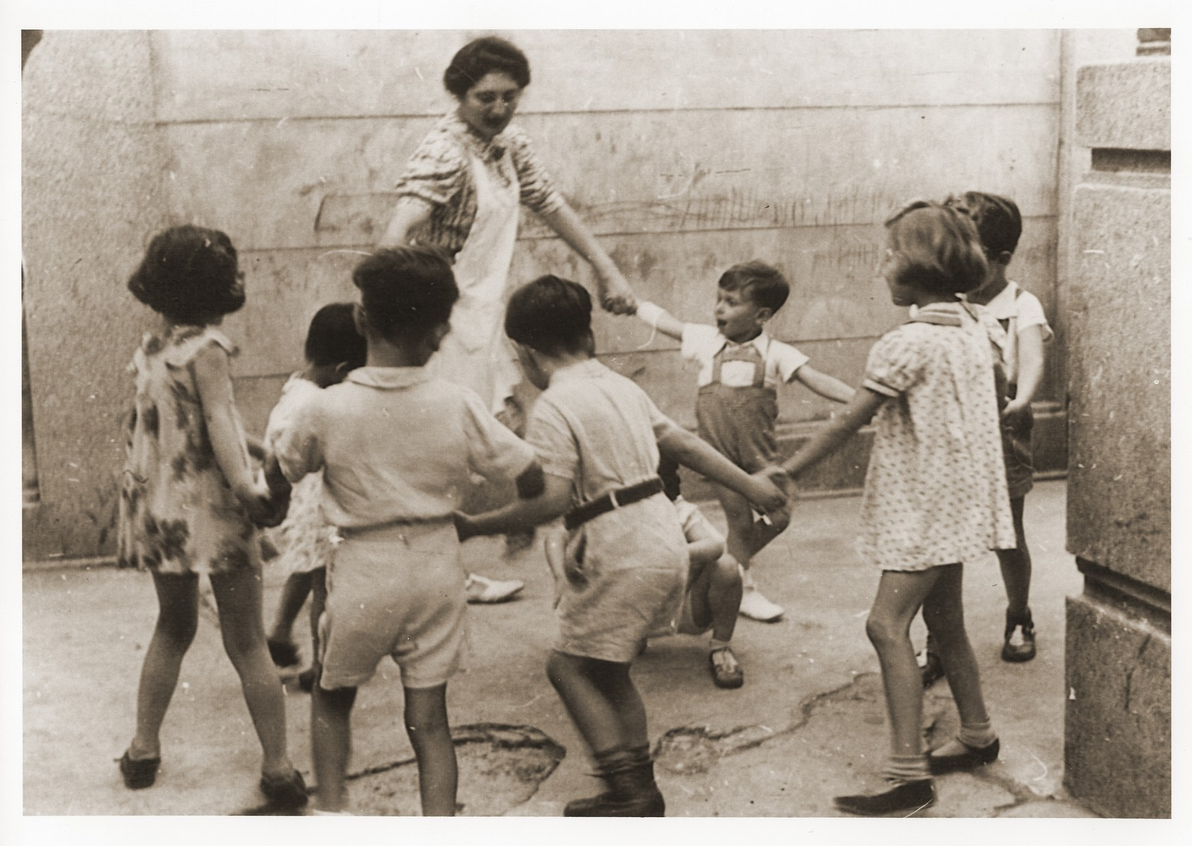 A teacher leads a group of young children in a circle dance at the Shanghai Jewish Youth Association School.  Among those pictured is Wolfgang Gotthelf (far right, partially hidden from view).  His aunt is the teacher.
