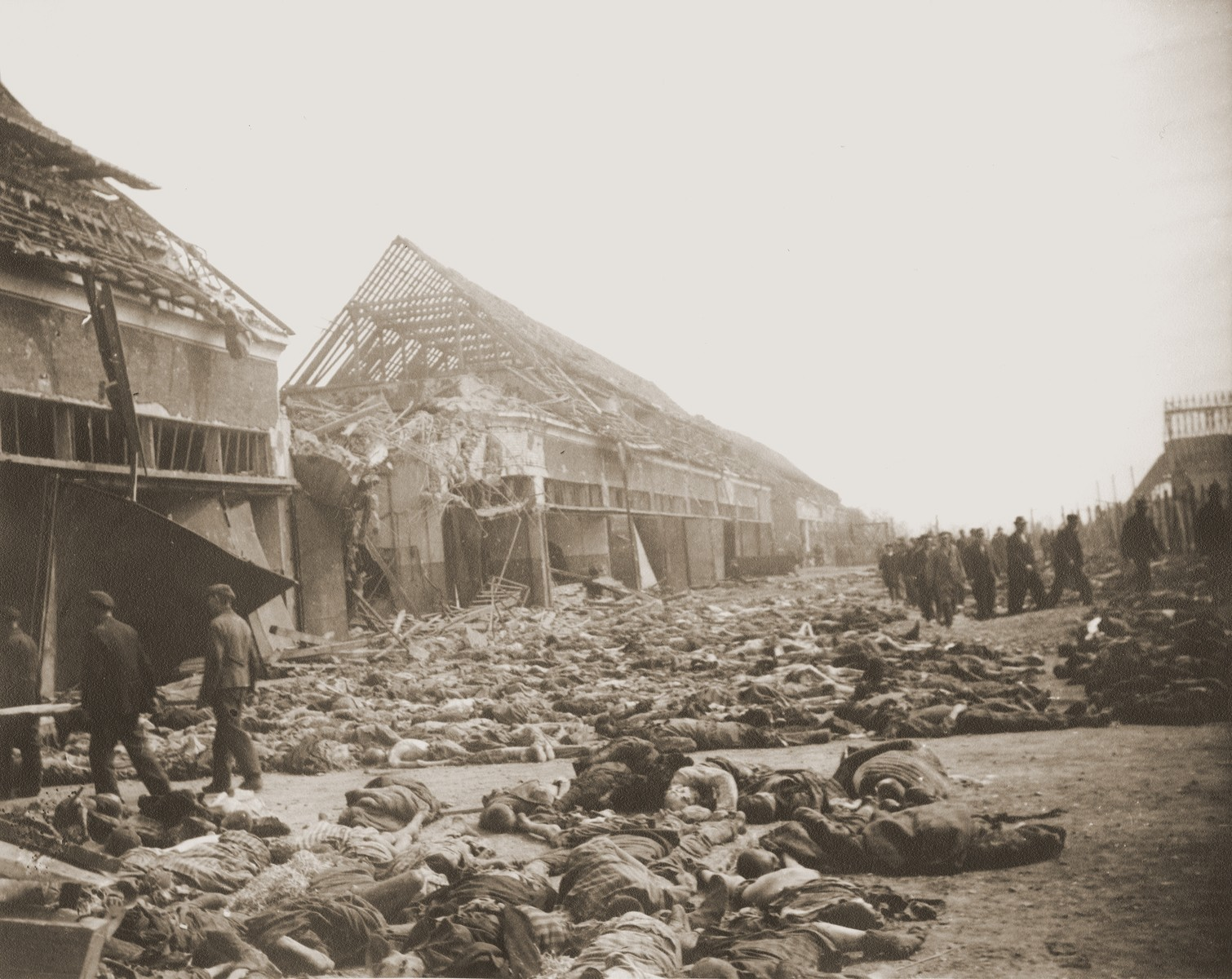 View of the main street of the Nordhausen concentration camp, outside of the central barracks (Boelke Kaserne), where the bodies of prisoners have been laid out in long rows.  German civilians are being forced to carry the corpses out of the barracks and into the street.