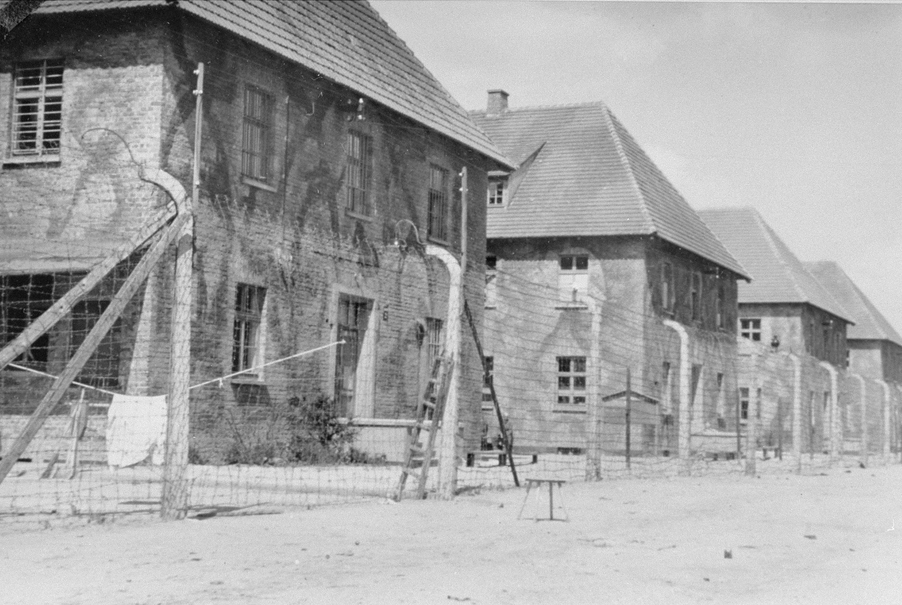"""View of the """"Canada"""" warehouses in Auschwitz I behind a barbed wire fence."""
