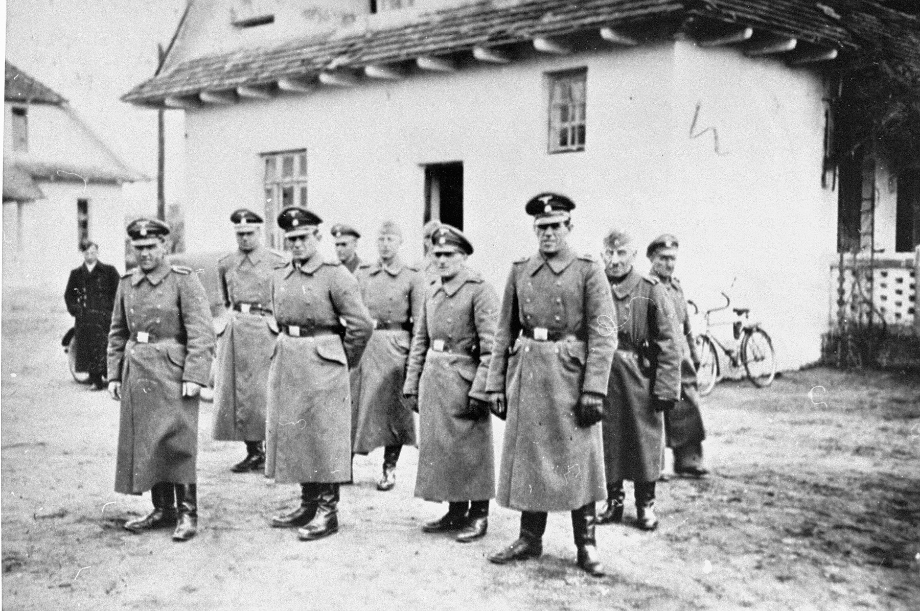 SS guards stand in formation outside the commandant's house near the Belzec concentration camp.    Pictured (in the front row from right to left) are:  SS Rottenfuehrer Heinrich Barbl and SS Oberwachmeister Artur Dachsel; (second row) SS Hauptscharfuehrer Lorenz Hackenholt, SS Unterscharfuehrer Ernst Zierke, SS Untersturmfuehrer Karl Gringers (front), and SS Untersturmfuehrer Fritz Tauscher (second from the left).