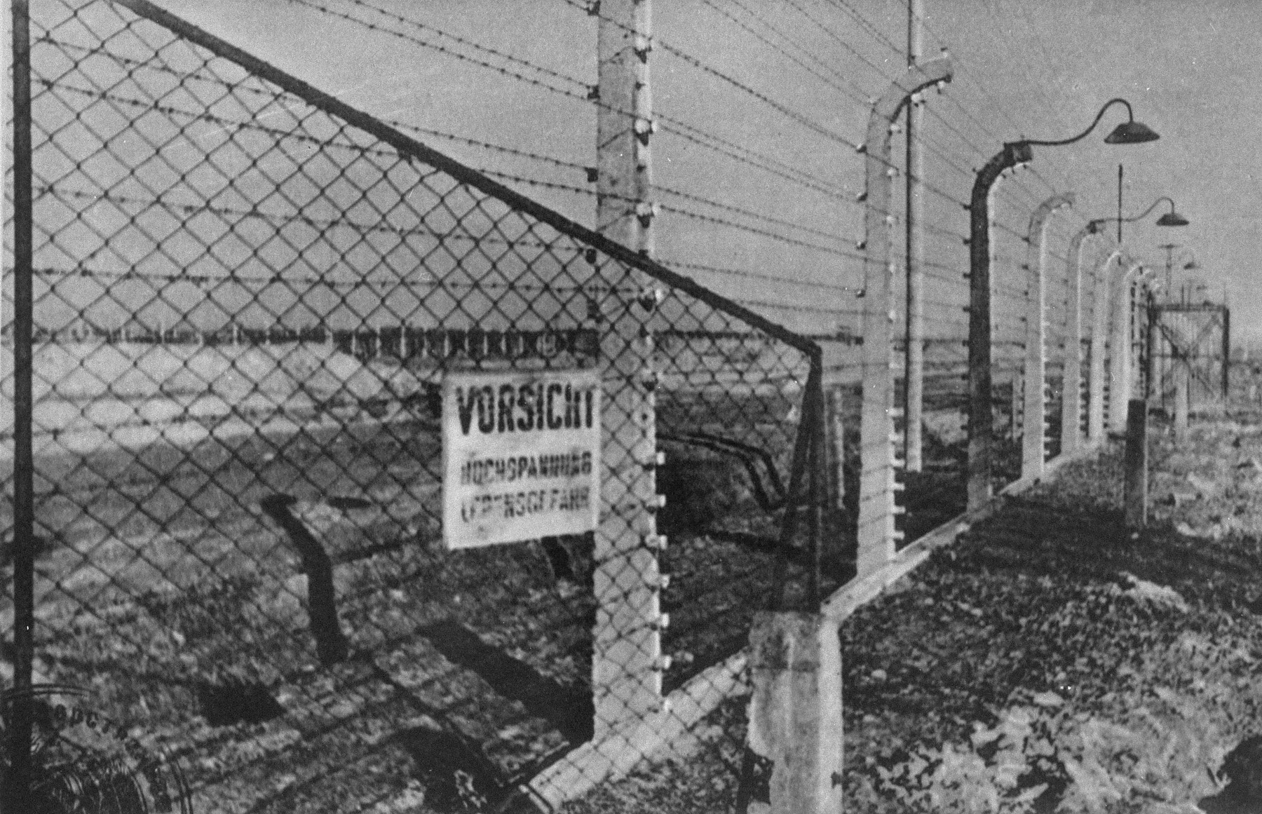 "A view of the electrified fence in Auschwitz.  The sign reads, ""Caution! High voltage. Danger to life."""