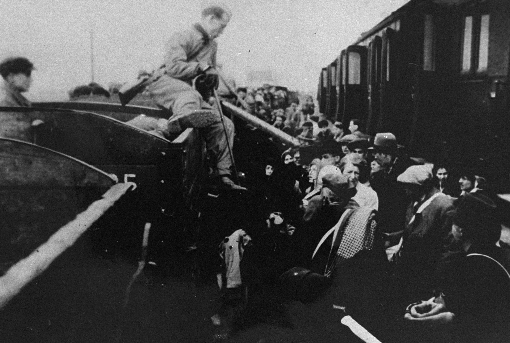 Jewish deportees from the Lodz ghetto who are being taken to the Chelmno death camp, are transferred from a closed passenger train to a train of open cars at the Kolo train station.