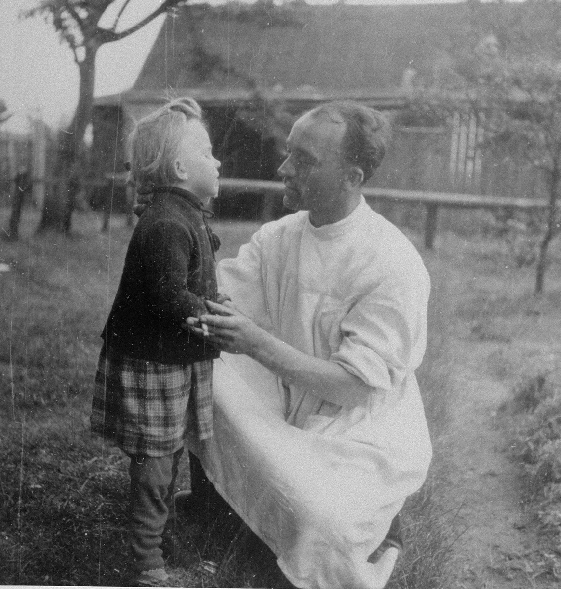 A physician looks at a little girl in theTrzebnia sub-camp of Auschwitz.