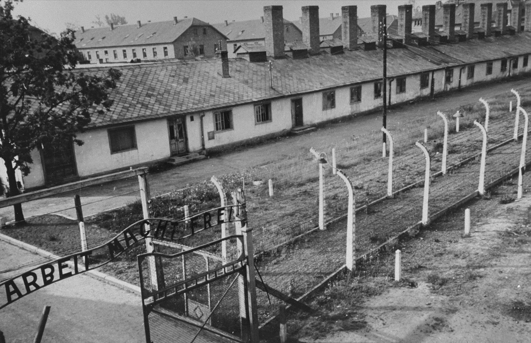 "View of the kitchen barracks, the electrified fence, and the gate at the main camp of Auschwitz (Auschwitz I).  In the foreground is the sign ""Arbeit Macht Frei"" (Work makes one free)."