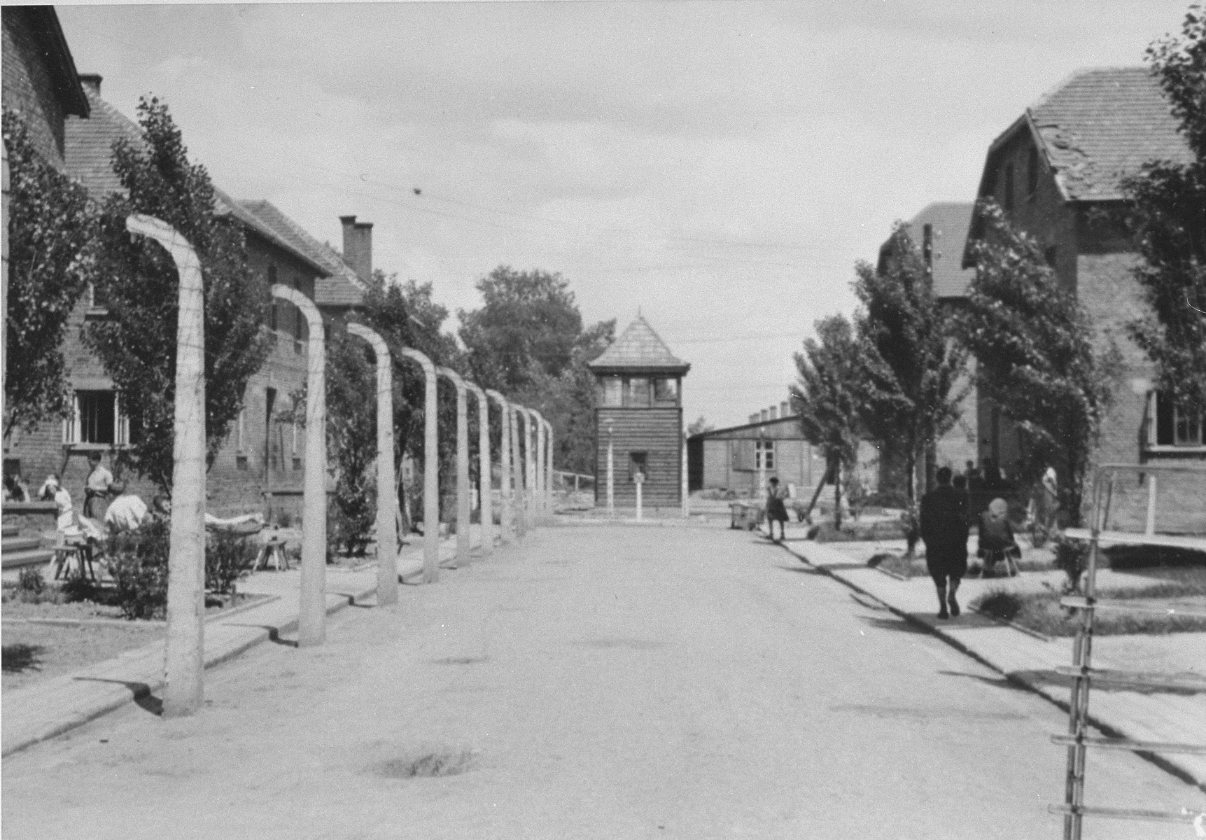 View of a road in the Auschwitz concentration camp separating rows of barracks and leading to a guard tower with, in the background, the crematorium I on the left and the Politische Abteilung's offices on the right.
