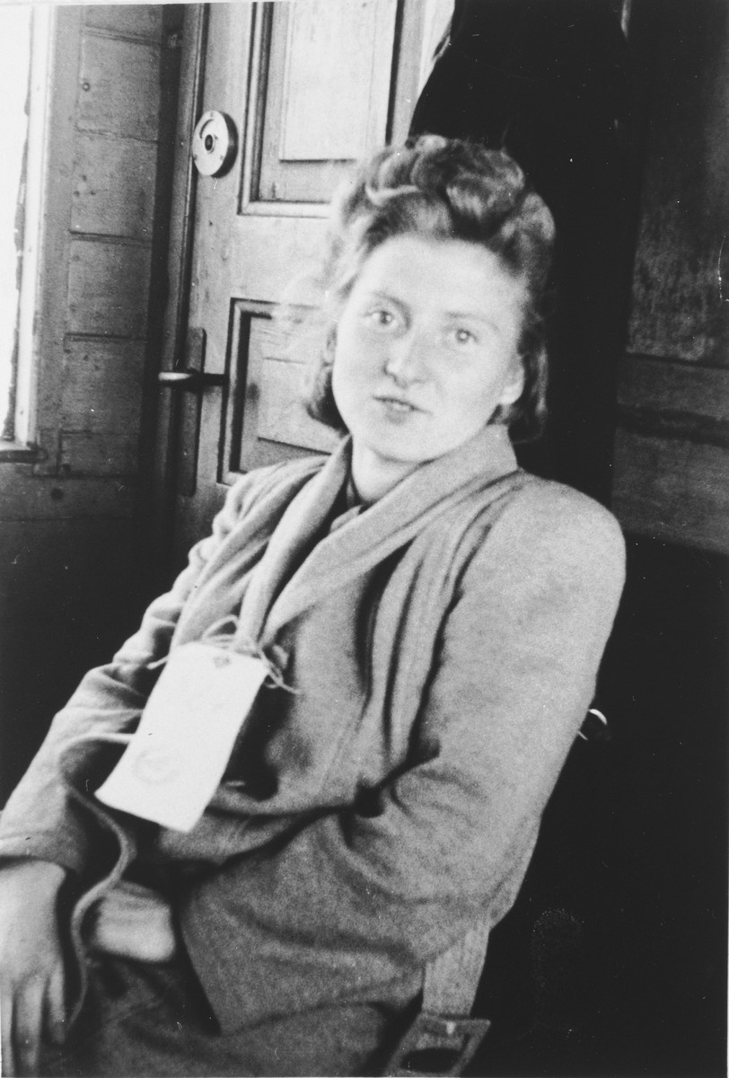 Eva (Mrowka) Sterner sits in a train station wearing a name tag while awaiting transport to Canada.