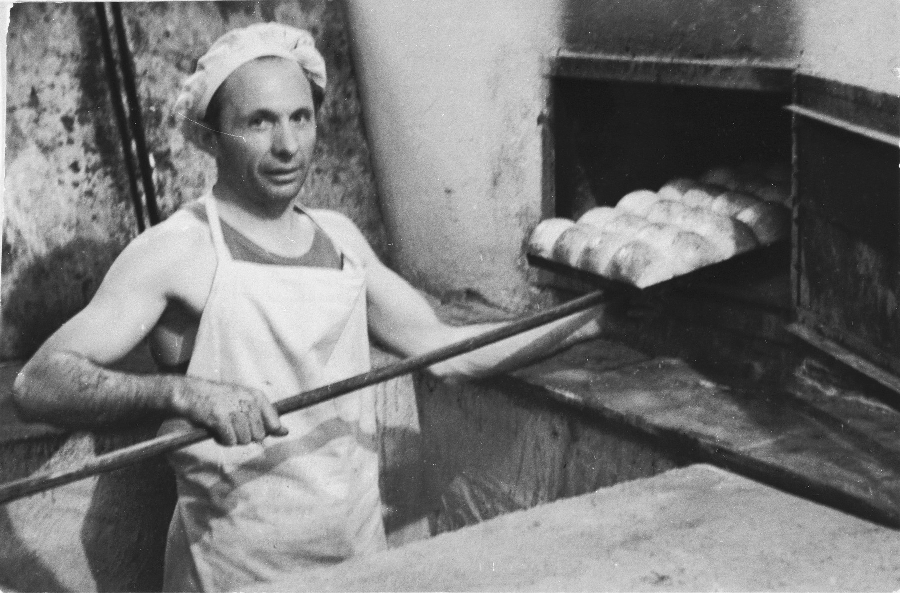 J. Weisblum removes a tray of breads from the oven at the Bindermichl displaced persons camp.